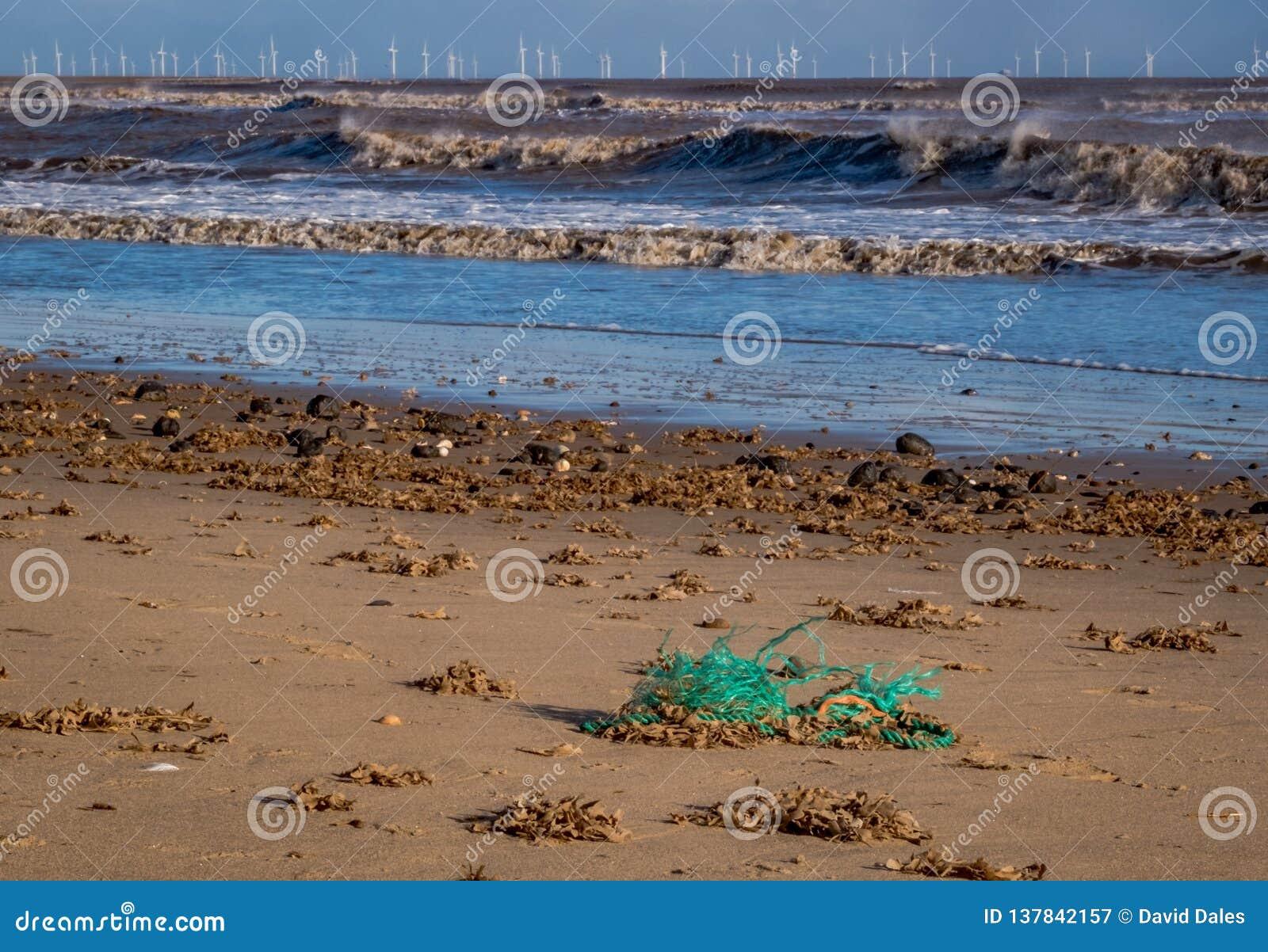 Windblown golven die op de kust met een windlandbouwbedrijf breken op de horizon