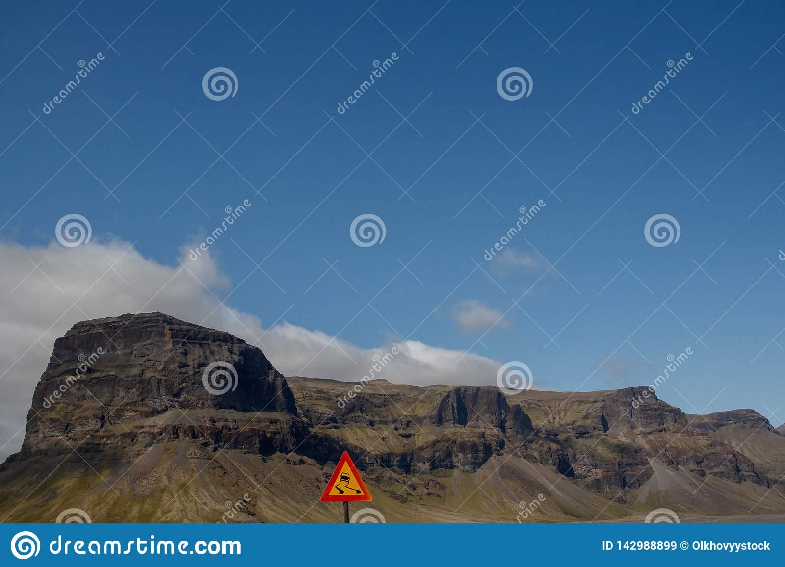 Winding road sign in and mountains on the background of the sky