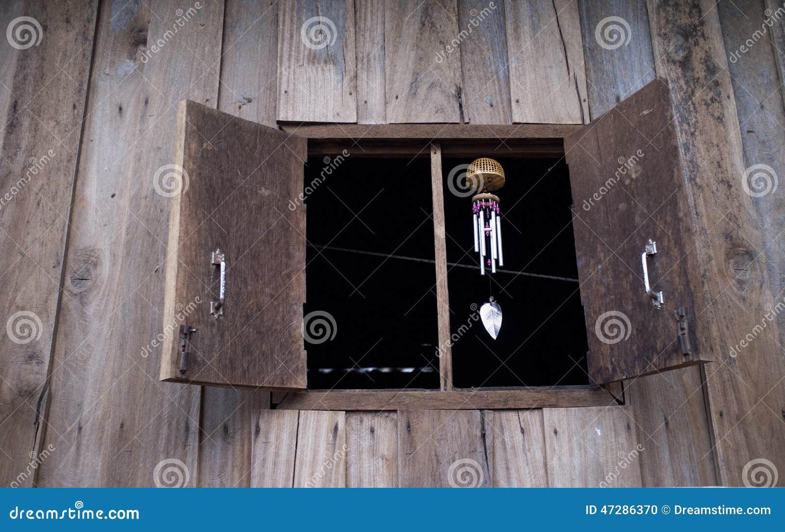 Windklokkengelui die op Houten venster hangen