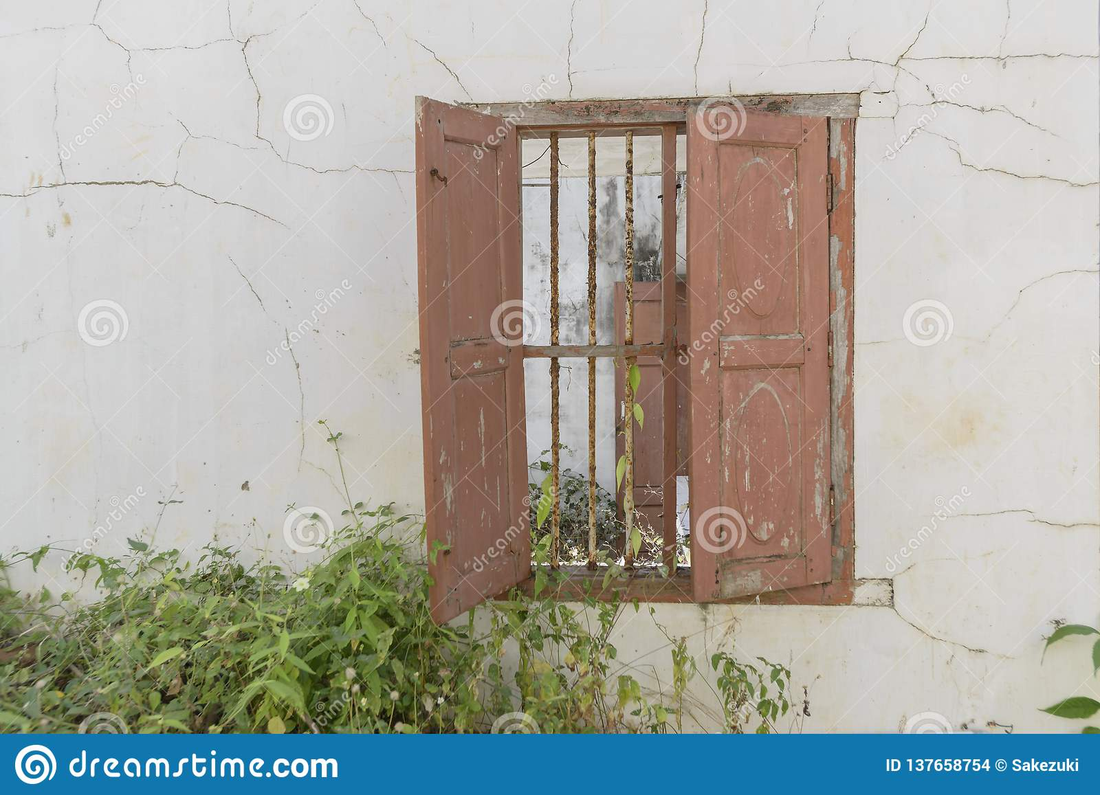 Window In An Old Abandoned House With Wooden Shutters And