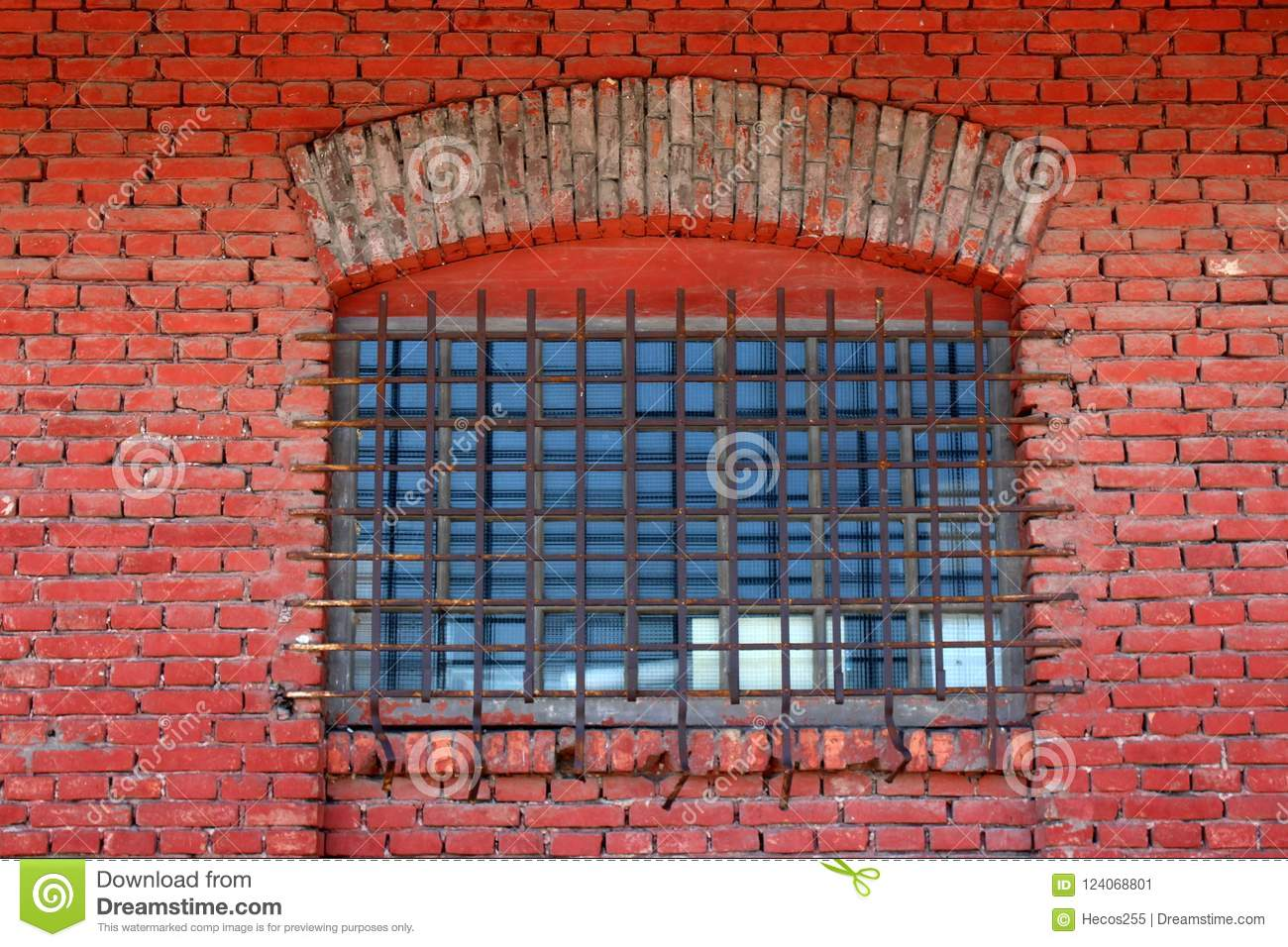 Window with safety wire protection and strong metal bars mounted on old red brick wall