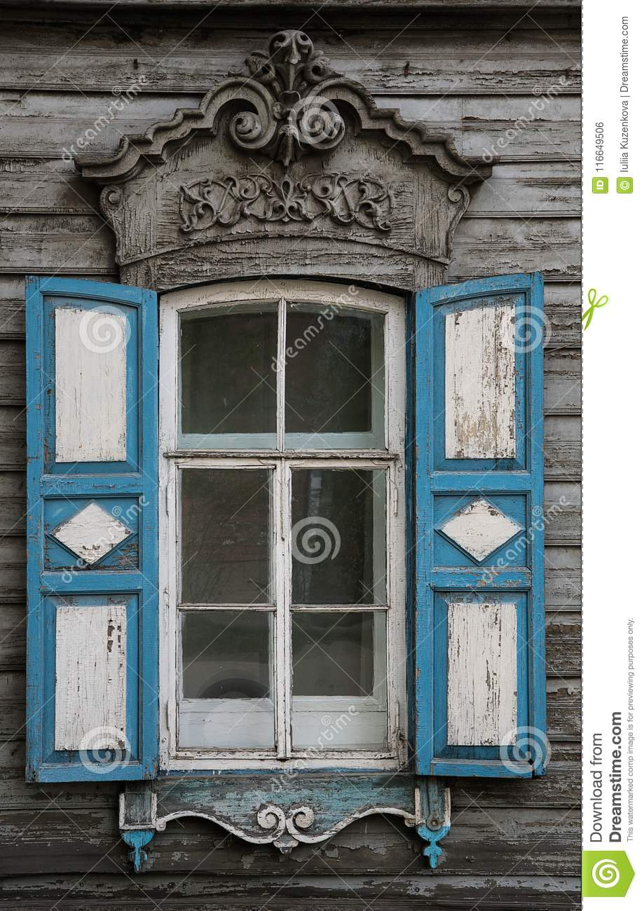 The window with the wooden carved architrave in the old wooden house in the old Russian town.