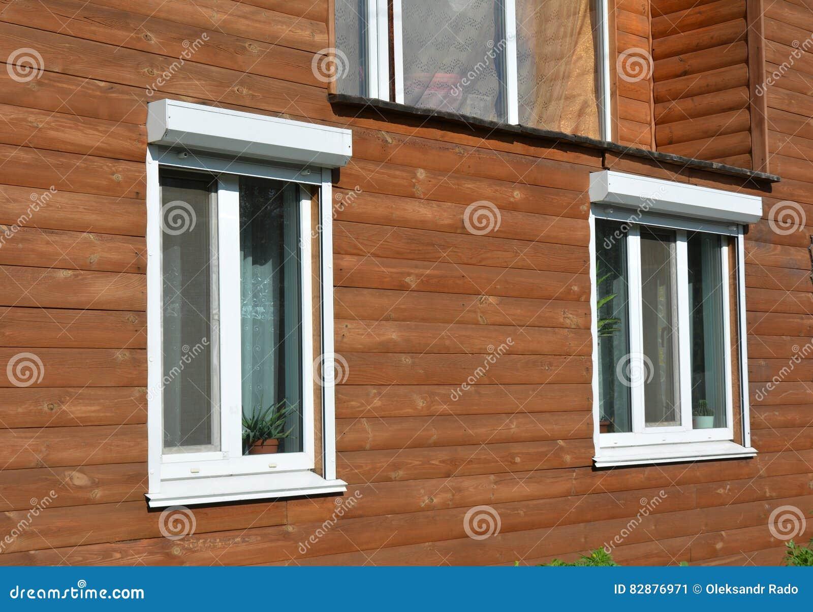 windows con la persiana enrrollable en el exterior de madera de la fachada de la casa
