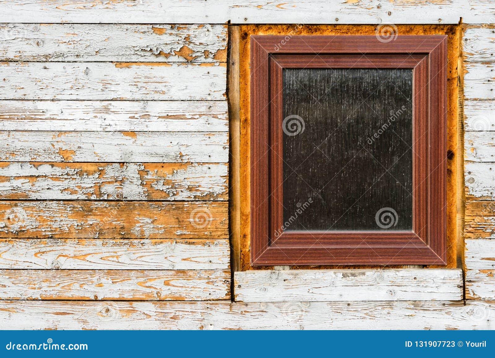Windows ha installato in vecchia casa di legno, sbucciando la pittura sulle plance di legno, indossanti la struttura