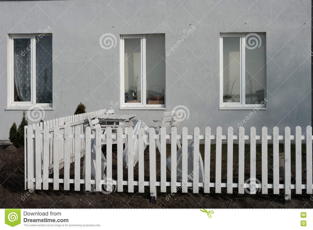 Windows, a white picket fence and garden furniture near the house