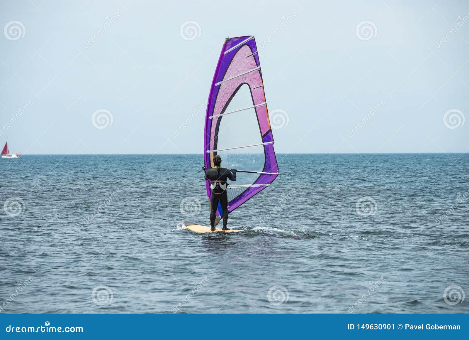 Windsurfer едет на море в спокойствие, светлом ветре