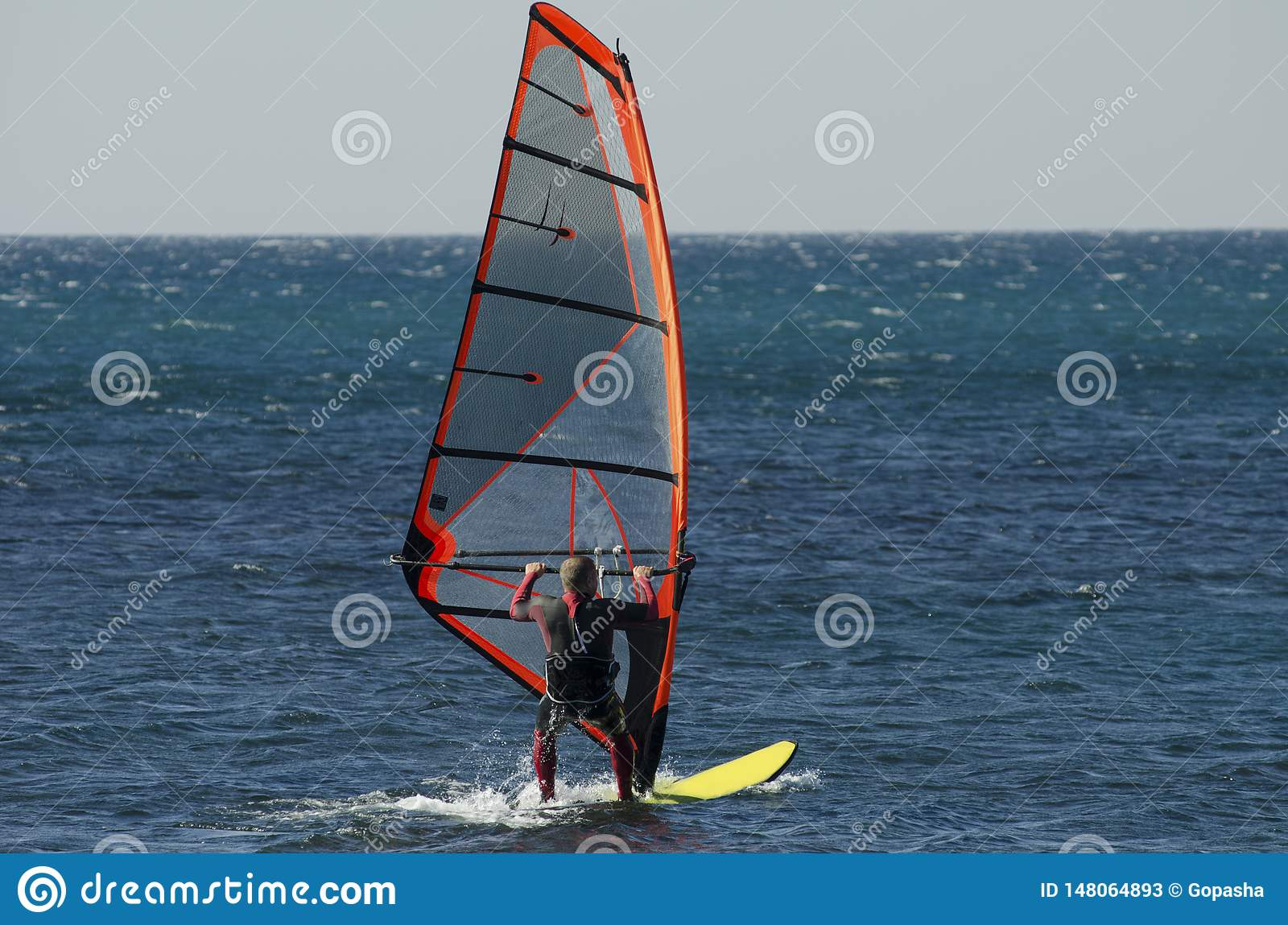 Windsurfing. A windsurfer rides on the sea in calm, light wind.