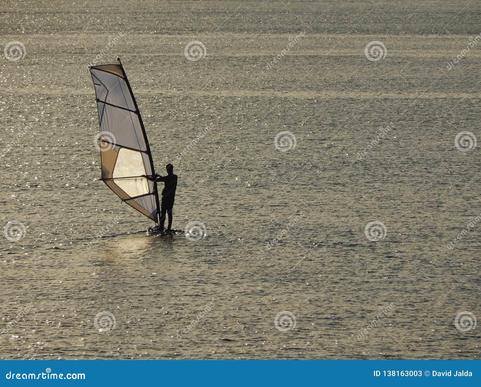 Windsurfing przy zmierzchem z spokojnym morzem