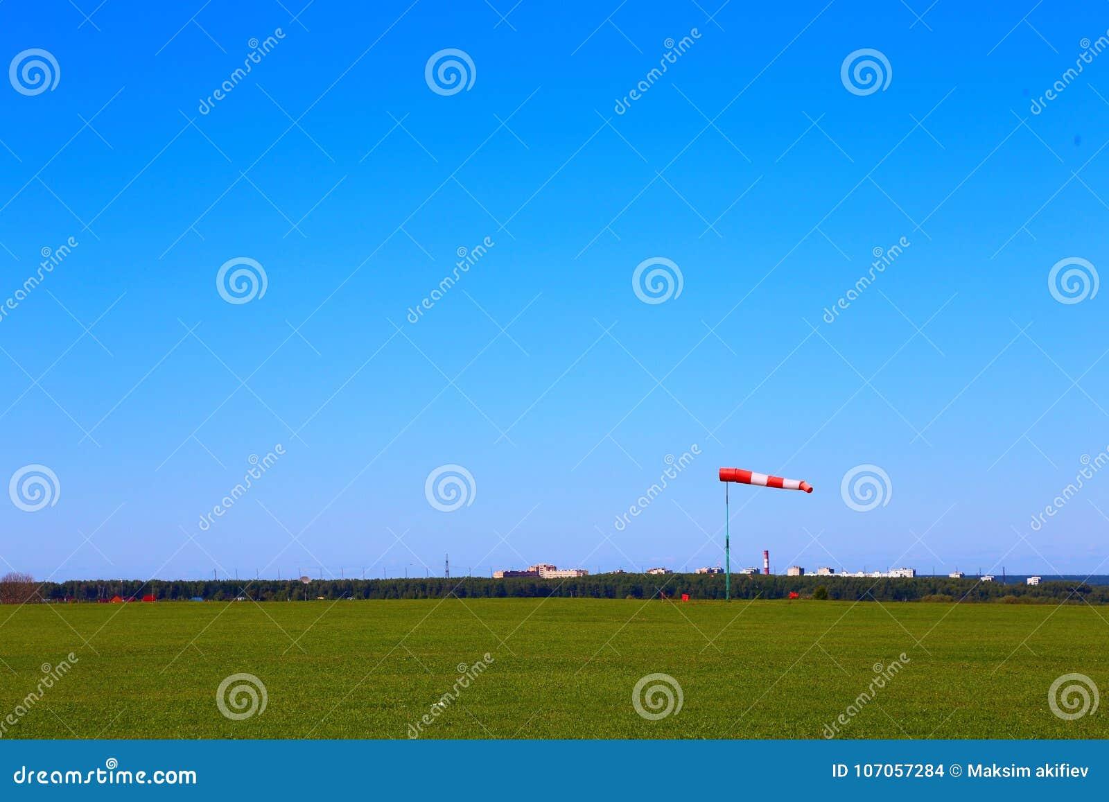 Windwijzer op het vliegveld tegen de hemel en het groene gras