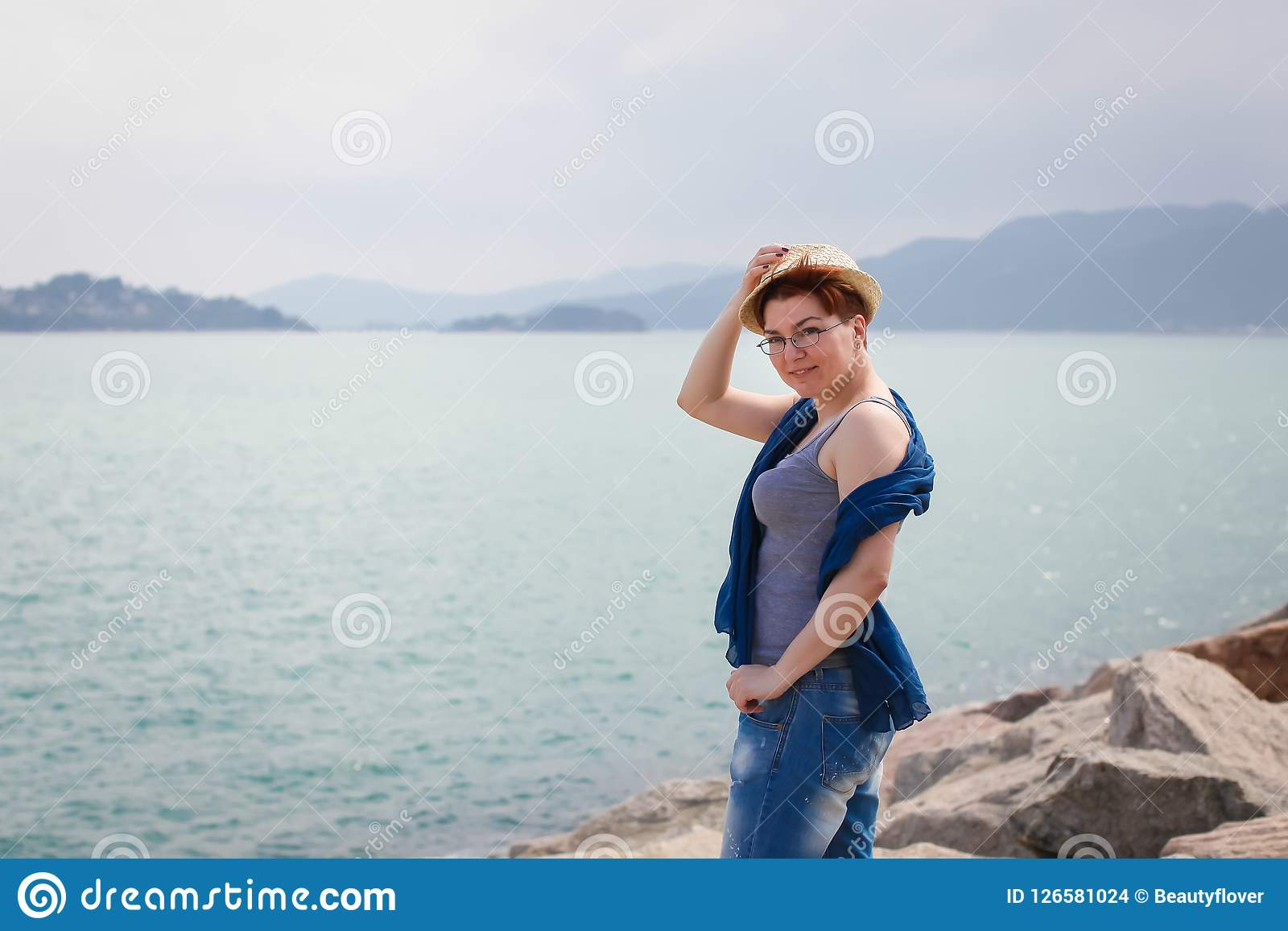 Windy summer days relaxing on coast feeling good. adult woman in glasses and jeans walks on the coast