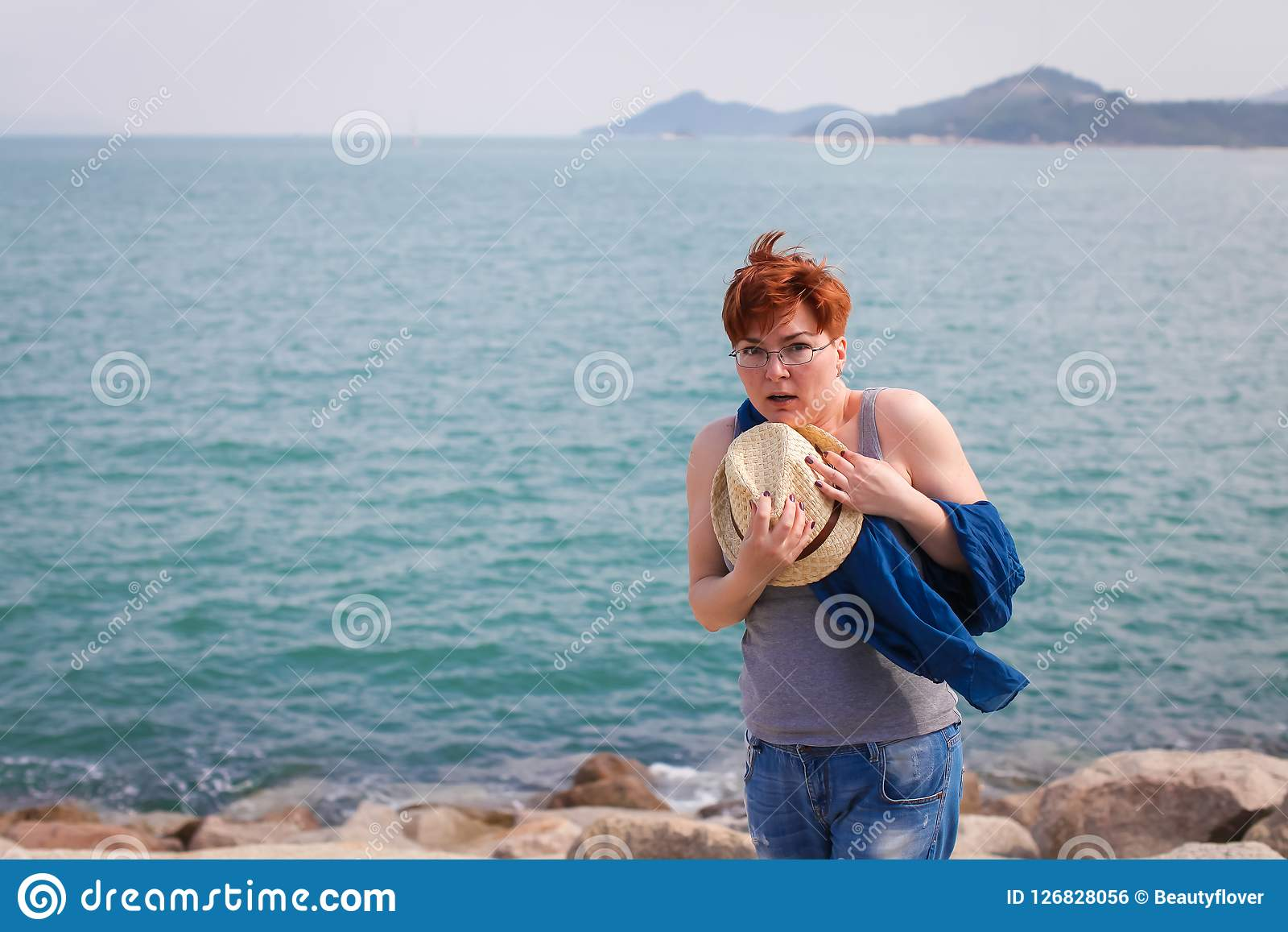 Windy summer days relaxing on coast feeling good. adult woman in glasses and jeans walks on the coast, portrays fright