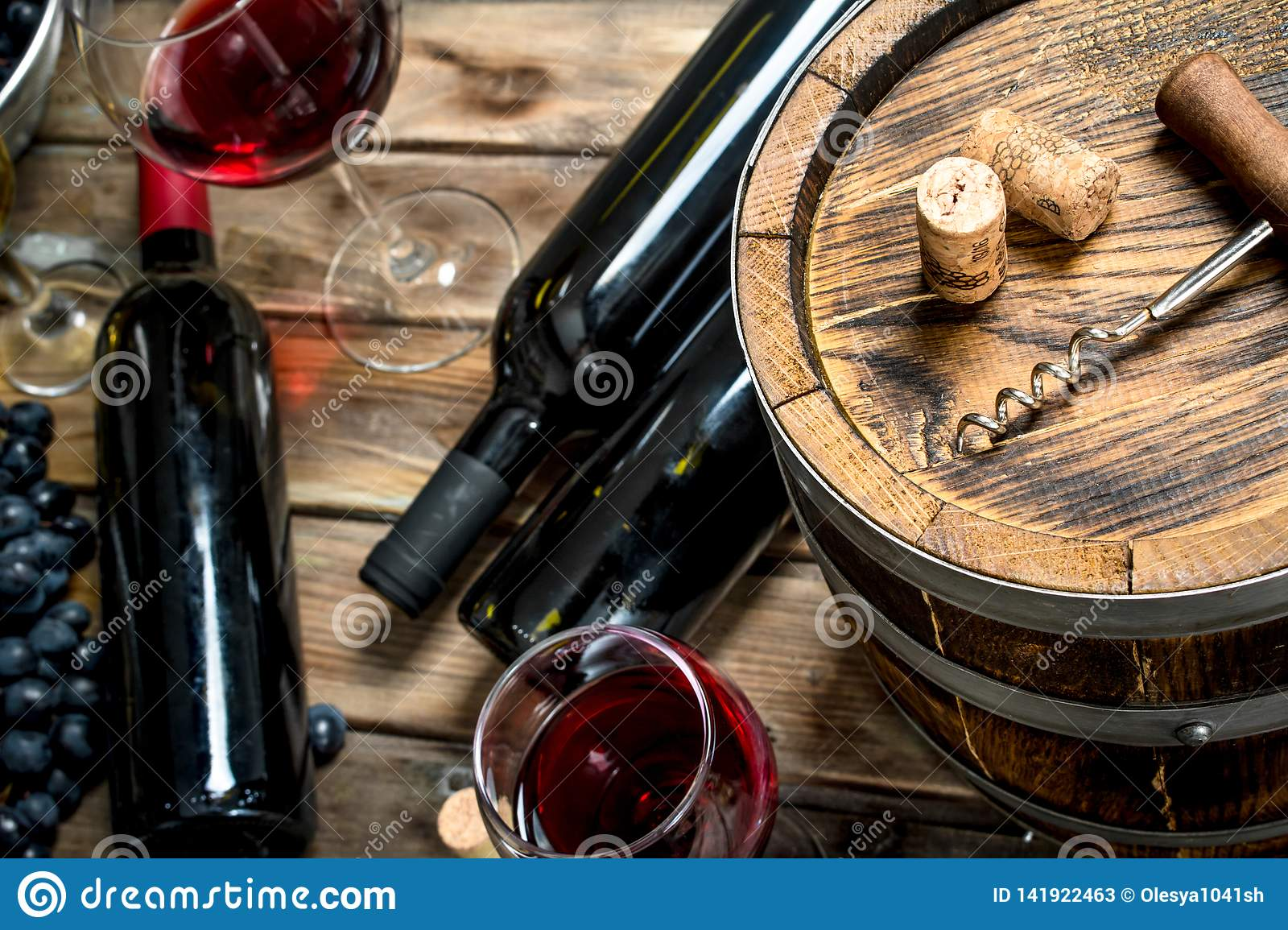 Wine background. Red wine with fresh grapes and an old barrel