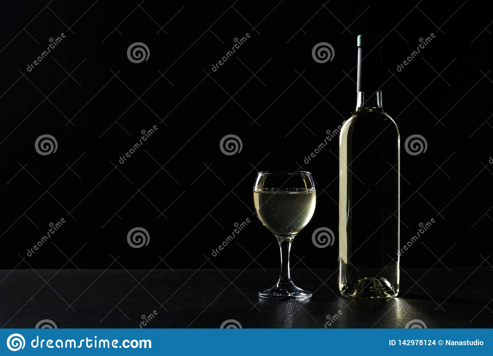 Wine bottle and glass with white wine on dark background