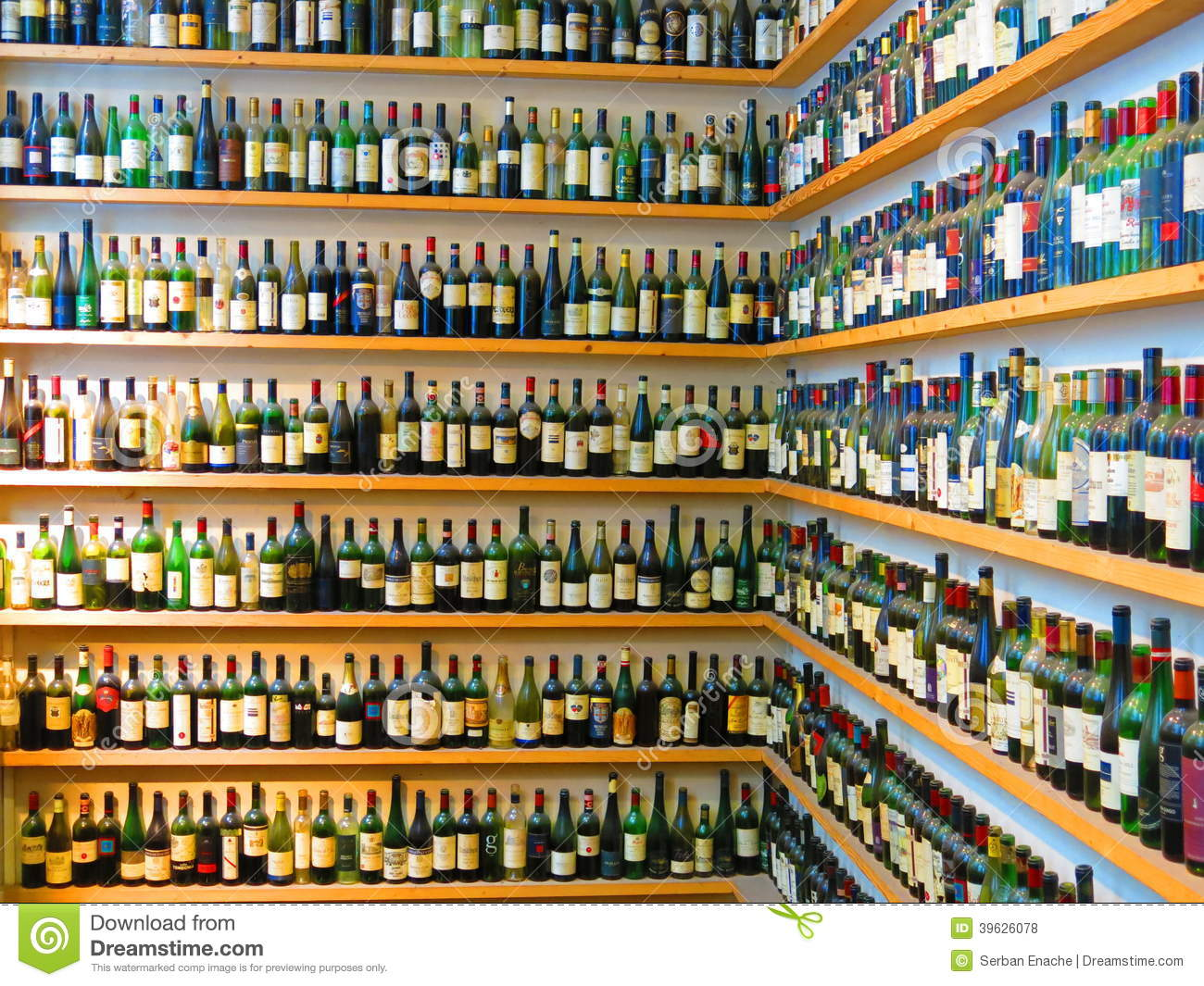 ... bottles lined up on two walls of shelves that meet at a right angle
