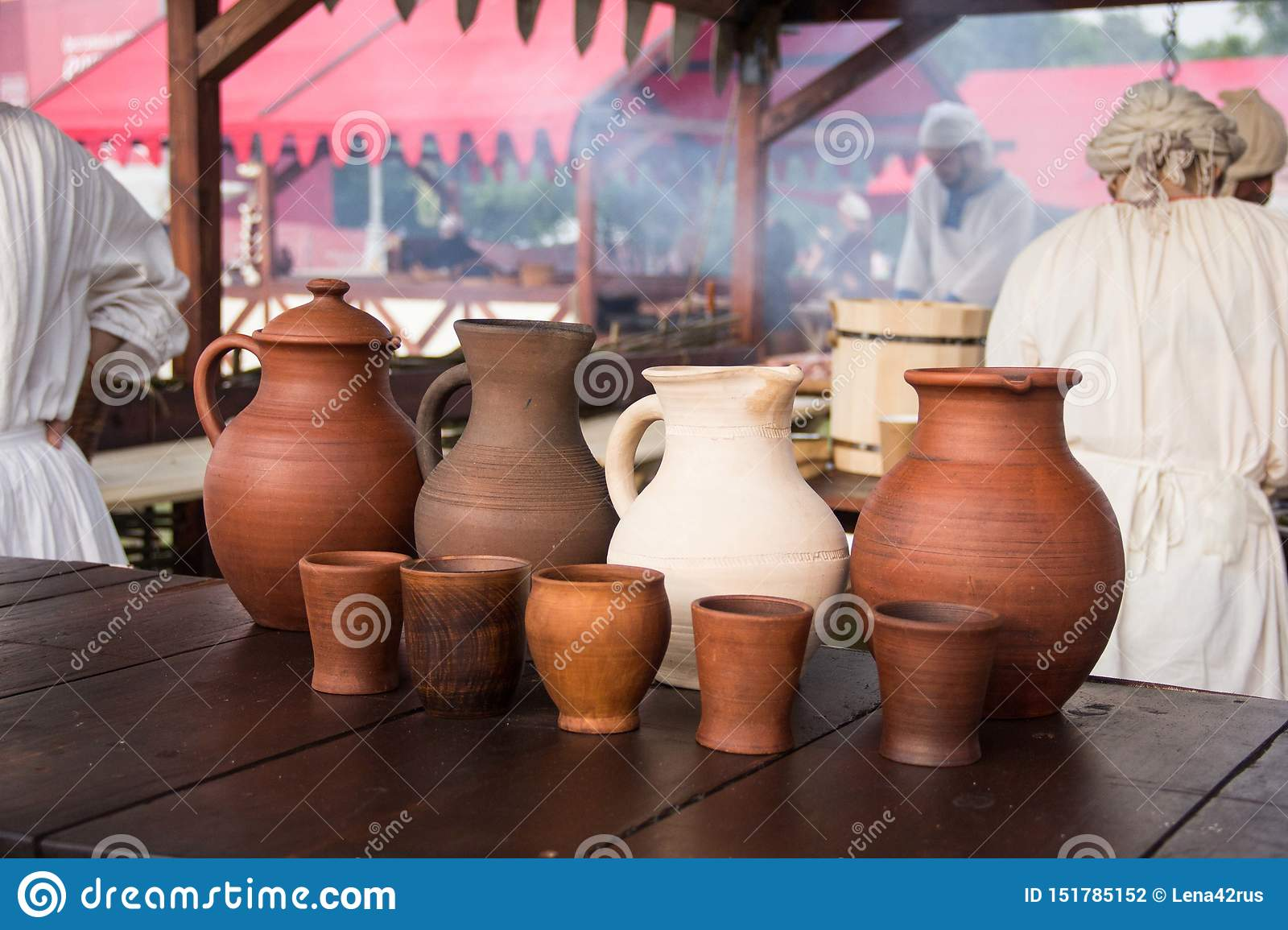 A wine jug and set of clay cups on the wooden table