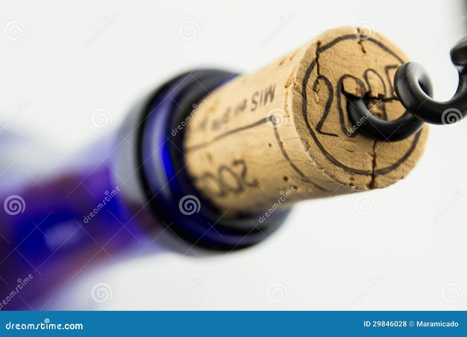 Vinho na garrafa azul com o corkscrew isolado
