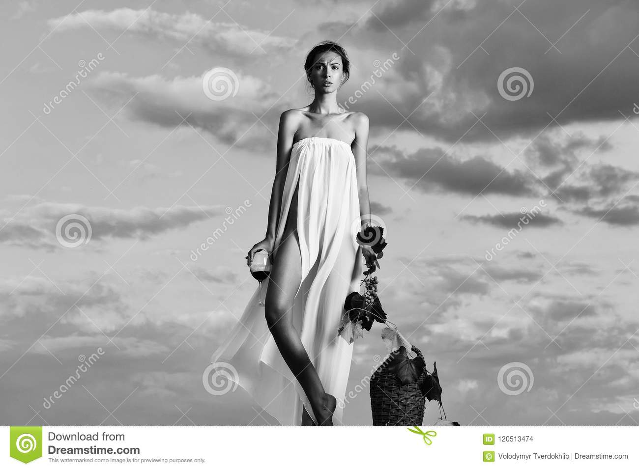 Pretty young girl or woman in white dress denuded with red wine in glass  wicker bottle vine and grapes on nature over blue sky
