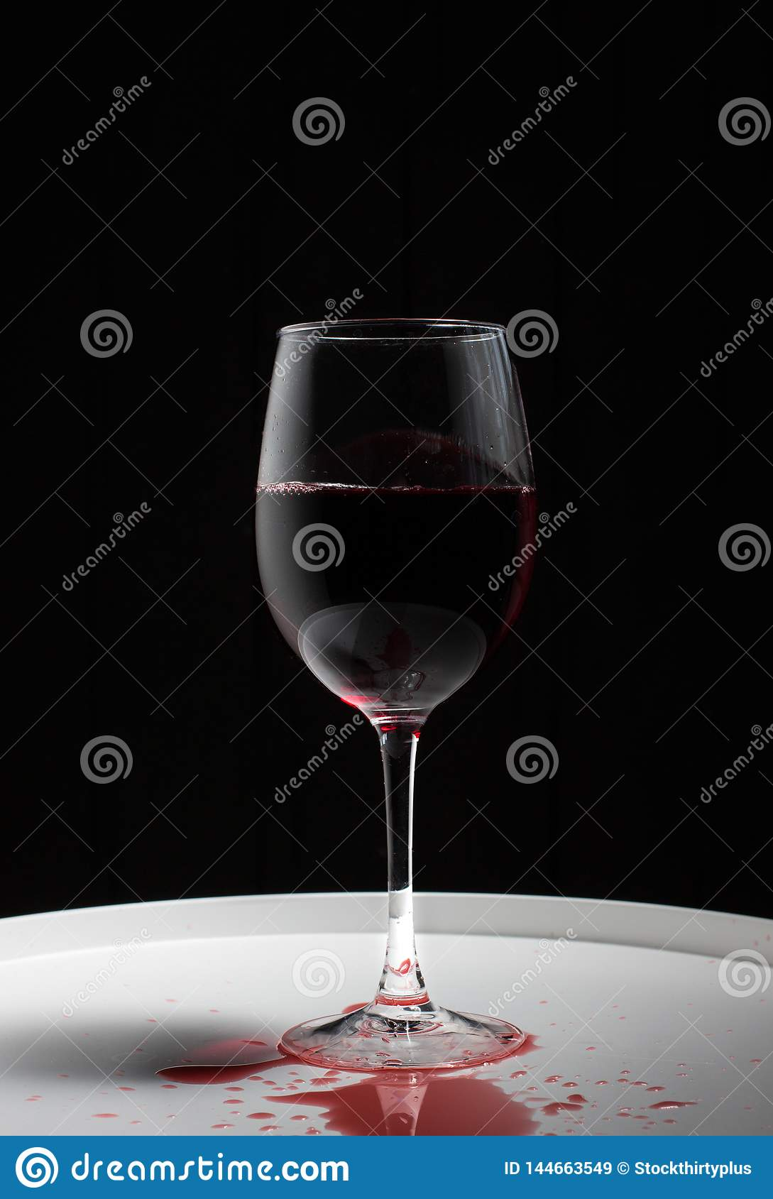 Wineglass with red wine on a white table