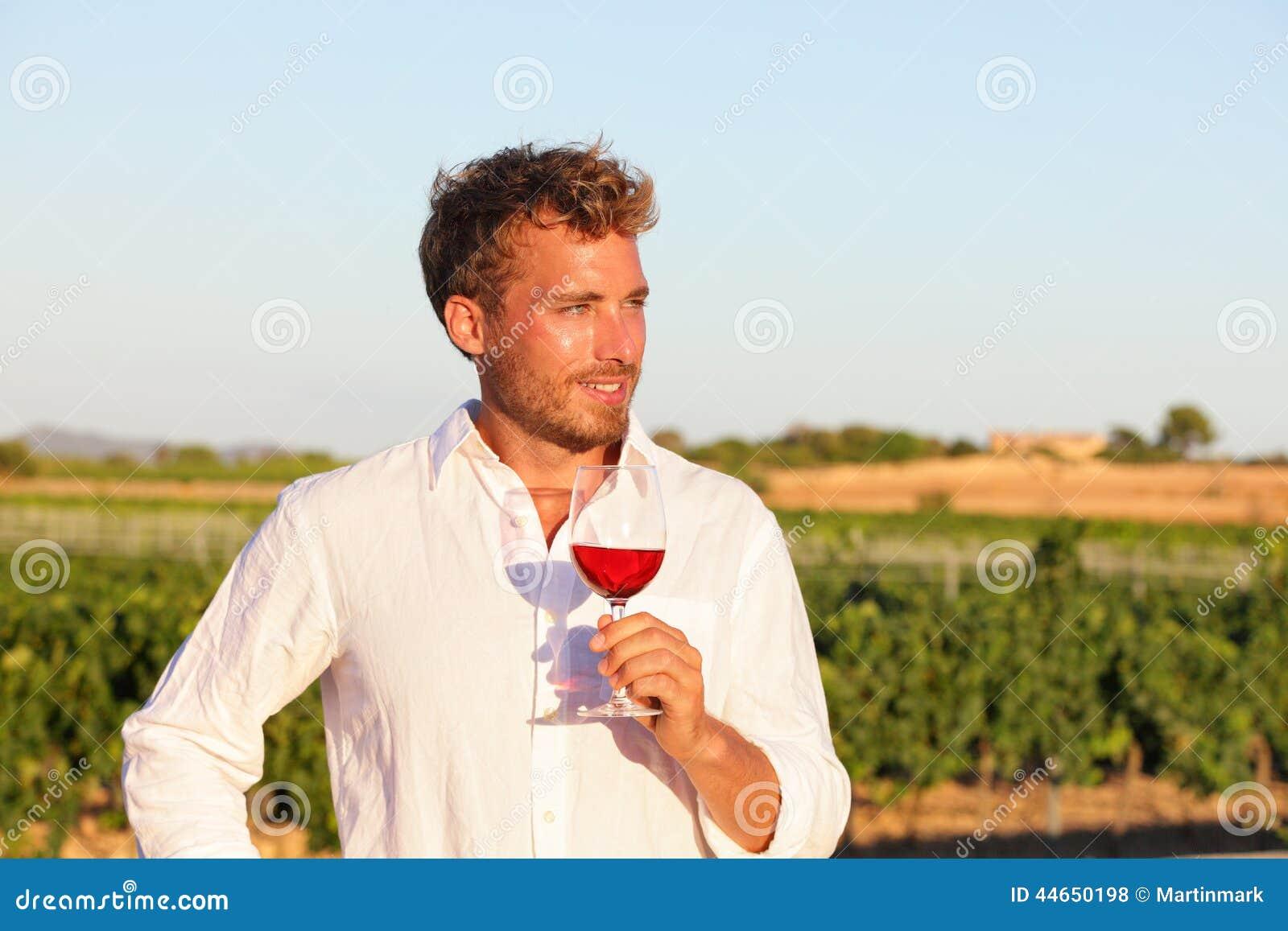 Winemaker man drinking rose or red wine, vineyard