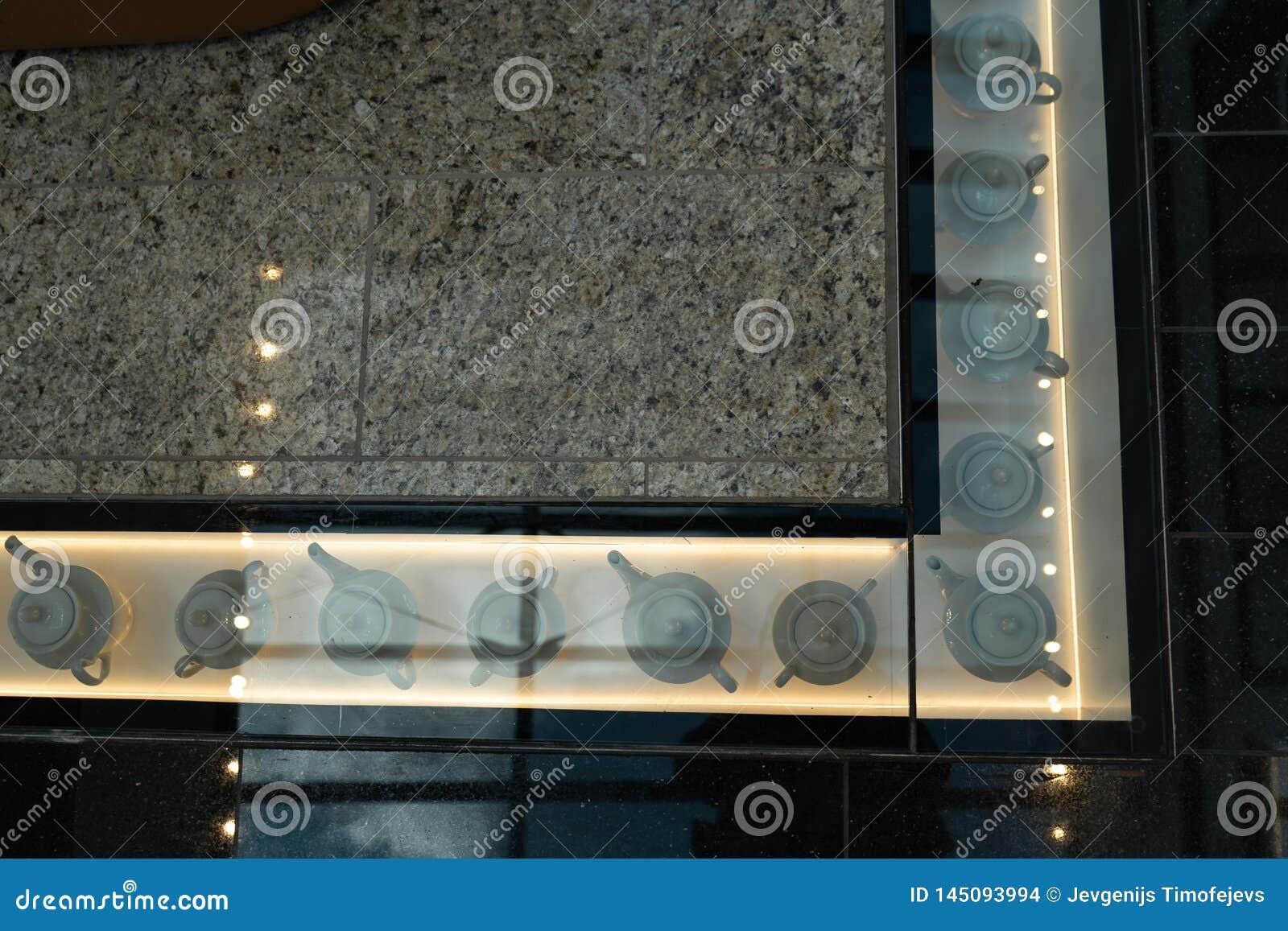 Winkelcomplexdecoratie - Theepotten onder een glasvloer