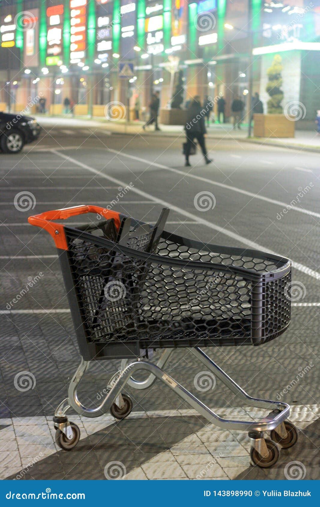 Winkelcomplexparkeerterrein en leeg boodschappenwagentje