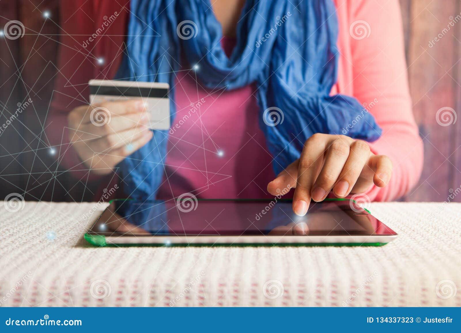 Winkelende online, mooie vrouw met creditcard het in hand betalen of het boeken in Internet