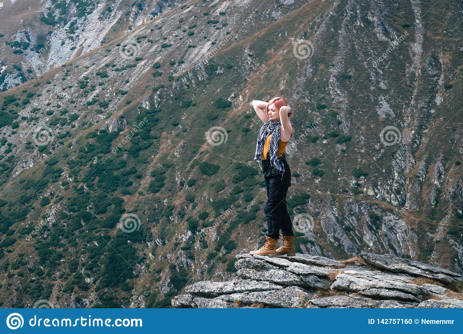 Winner. Success concept. Hiker girl after hiking to mountain top. copy space. adventure Romania