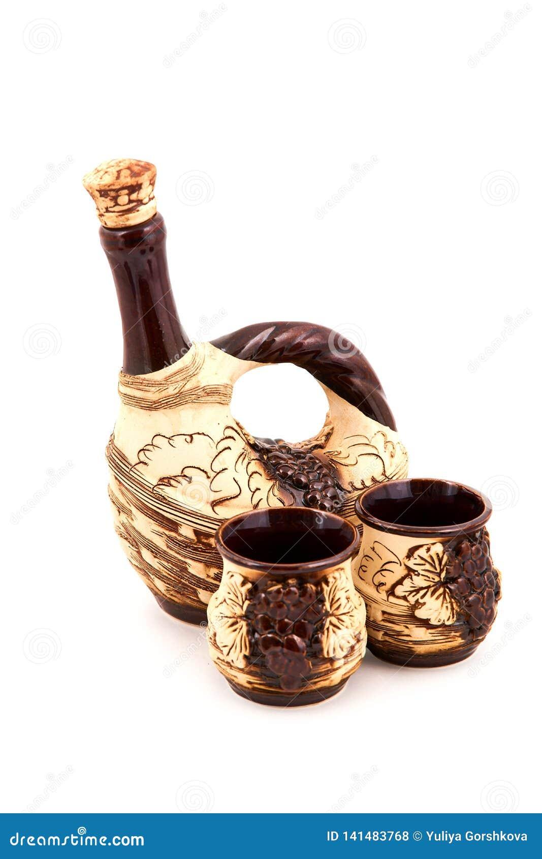Wino dzbanek i dwa handmade kubka odizolowywających na białym tle z ścinek ścieżką