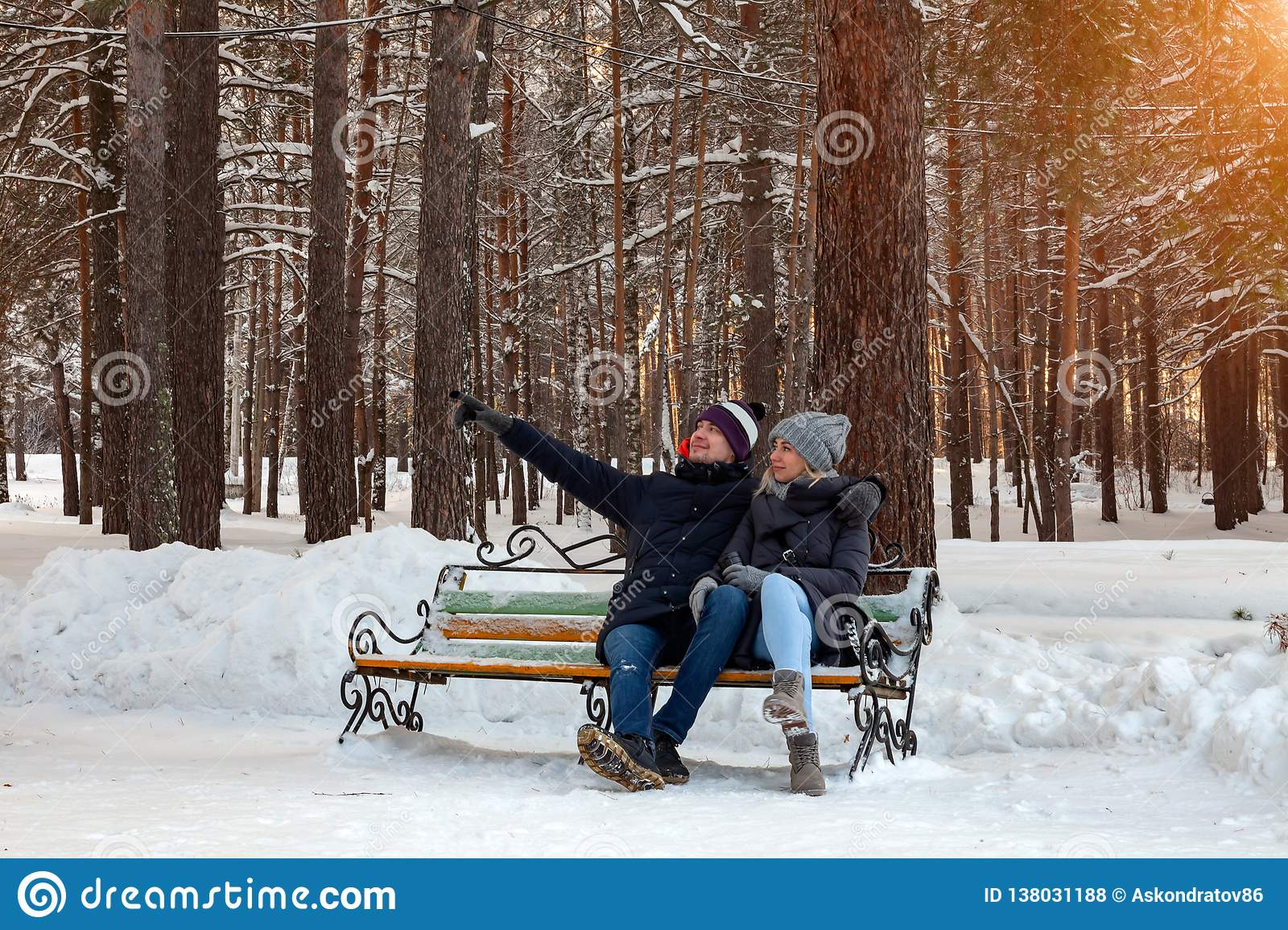 ee967e04 In The Winter Afternoon, A Loving Couple In Jackets And Hats Are ...