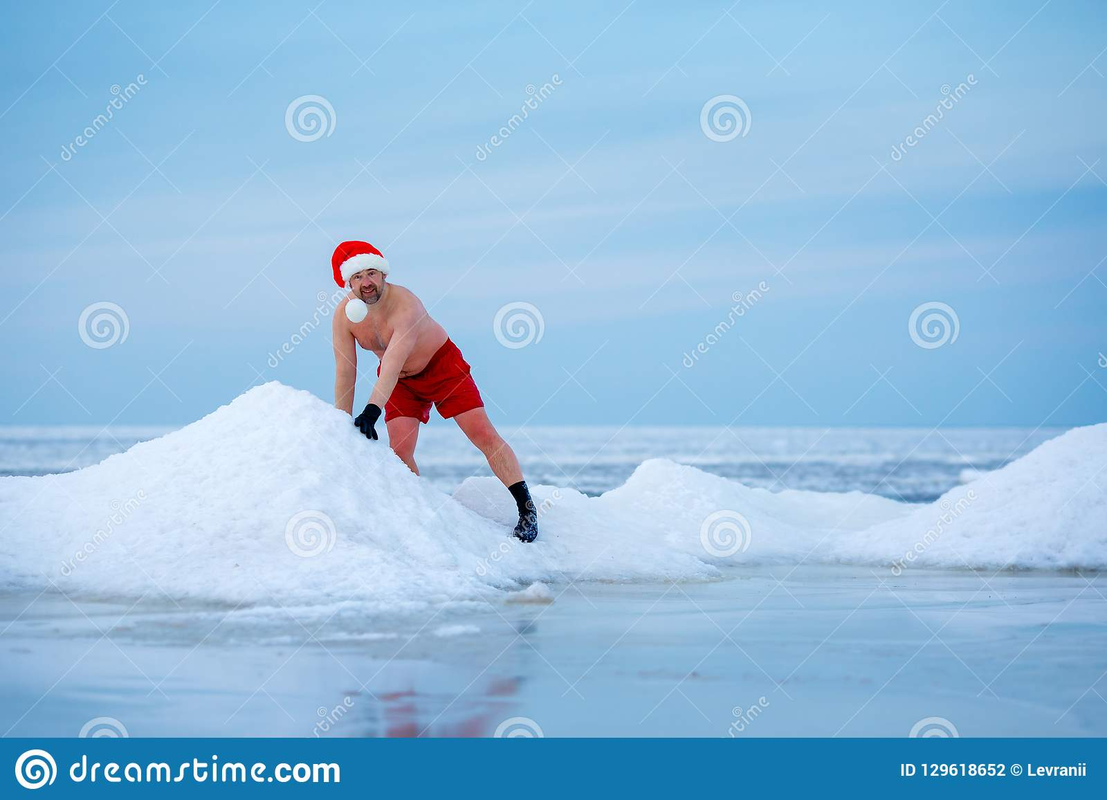 ef99c1409d5 Winter bather in a Santa`s hat stays in a frozen sea. Healthy lifestyle.  Christmas celebration