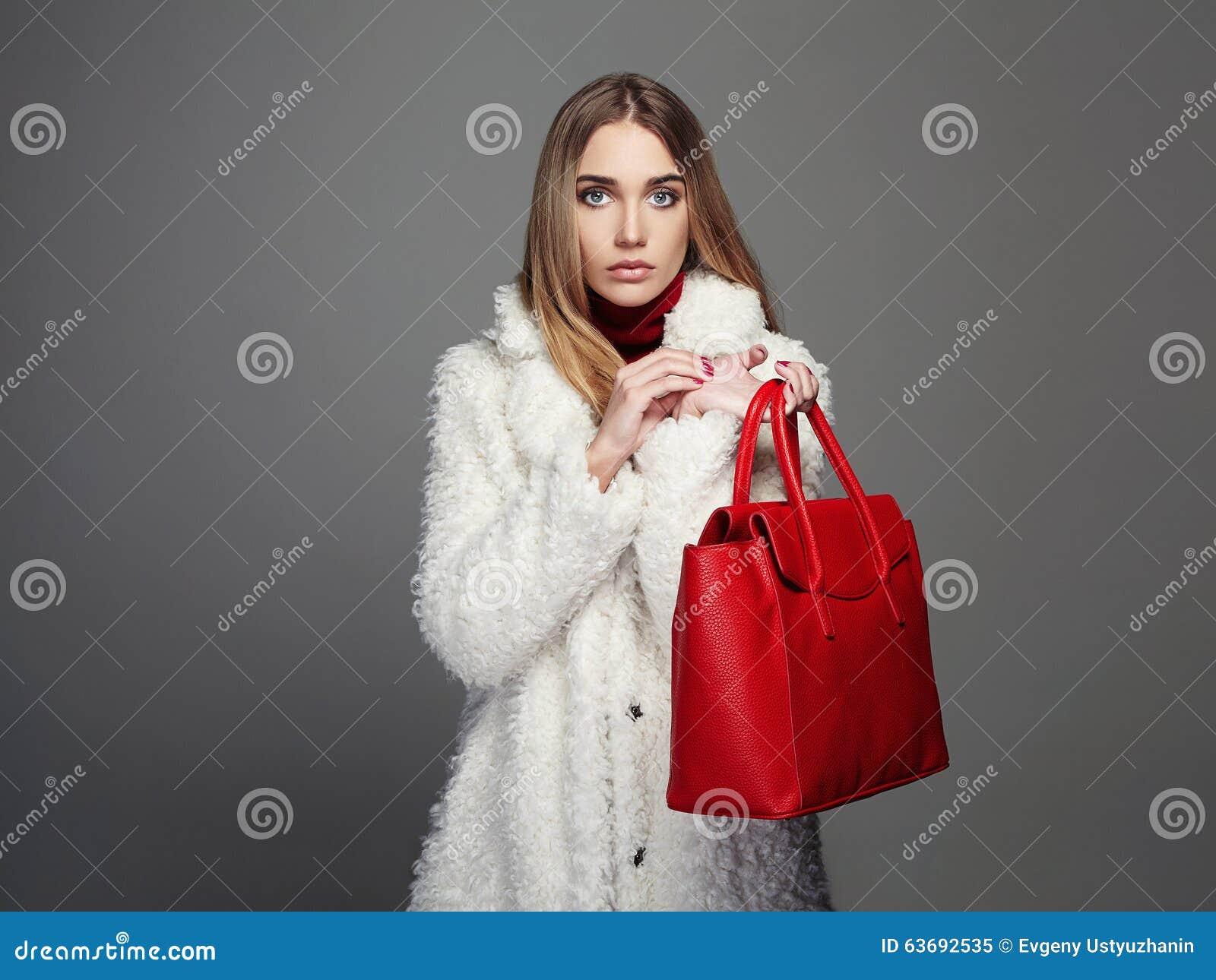 Winter beautiful Woman with red Handbag. Beauty Fashion Model Girl in fur