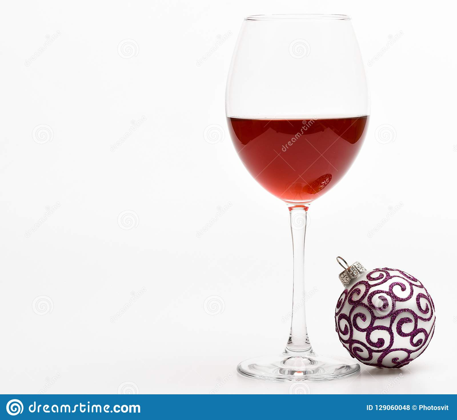 Winter celebration with alcohol drink. New year party concept. Wineglass with red liquid or wine and christmas ball