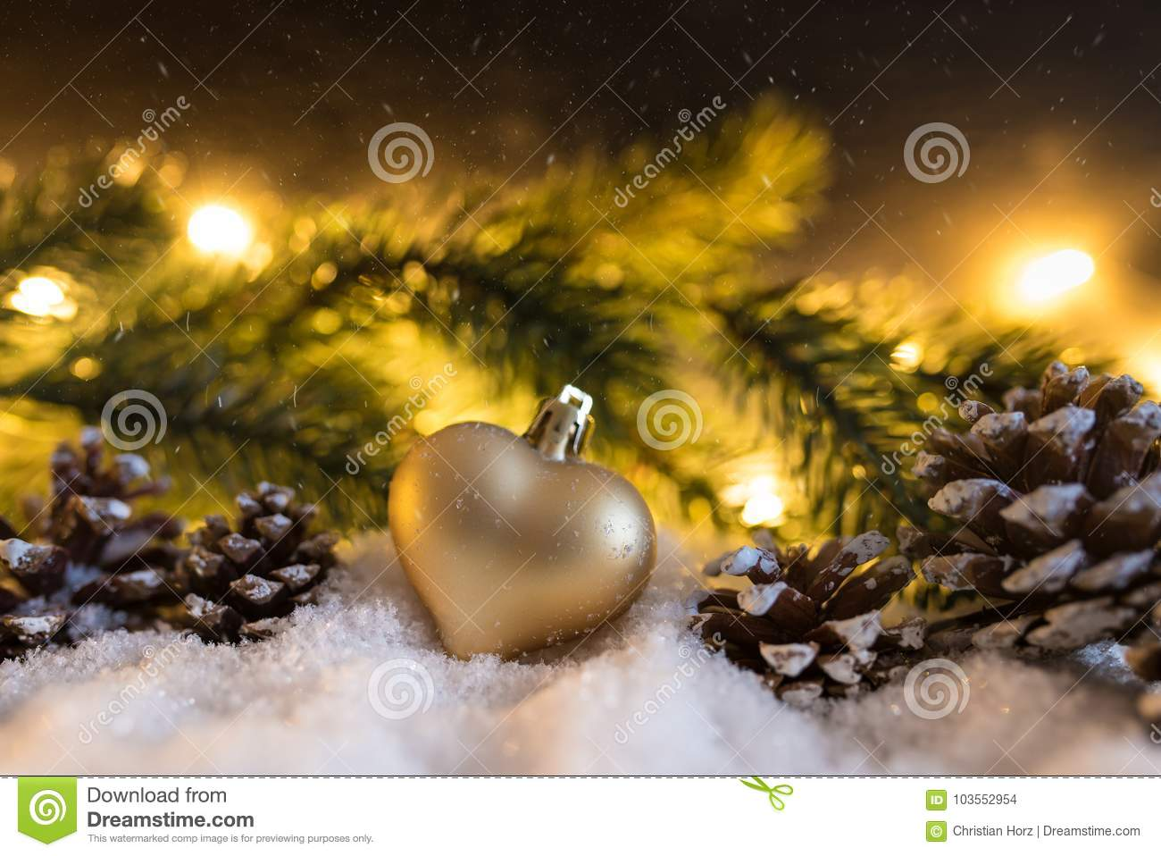 Winter christmas decoration with heart shaped christmas ornament, cones, fir branch and glowing lights