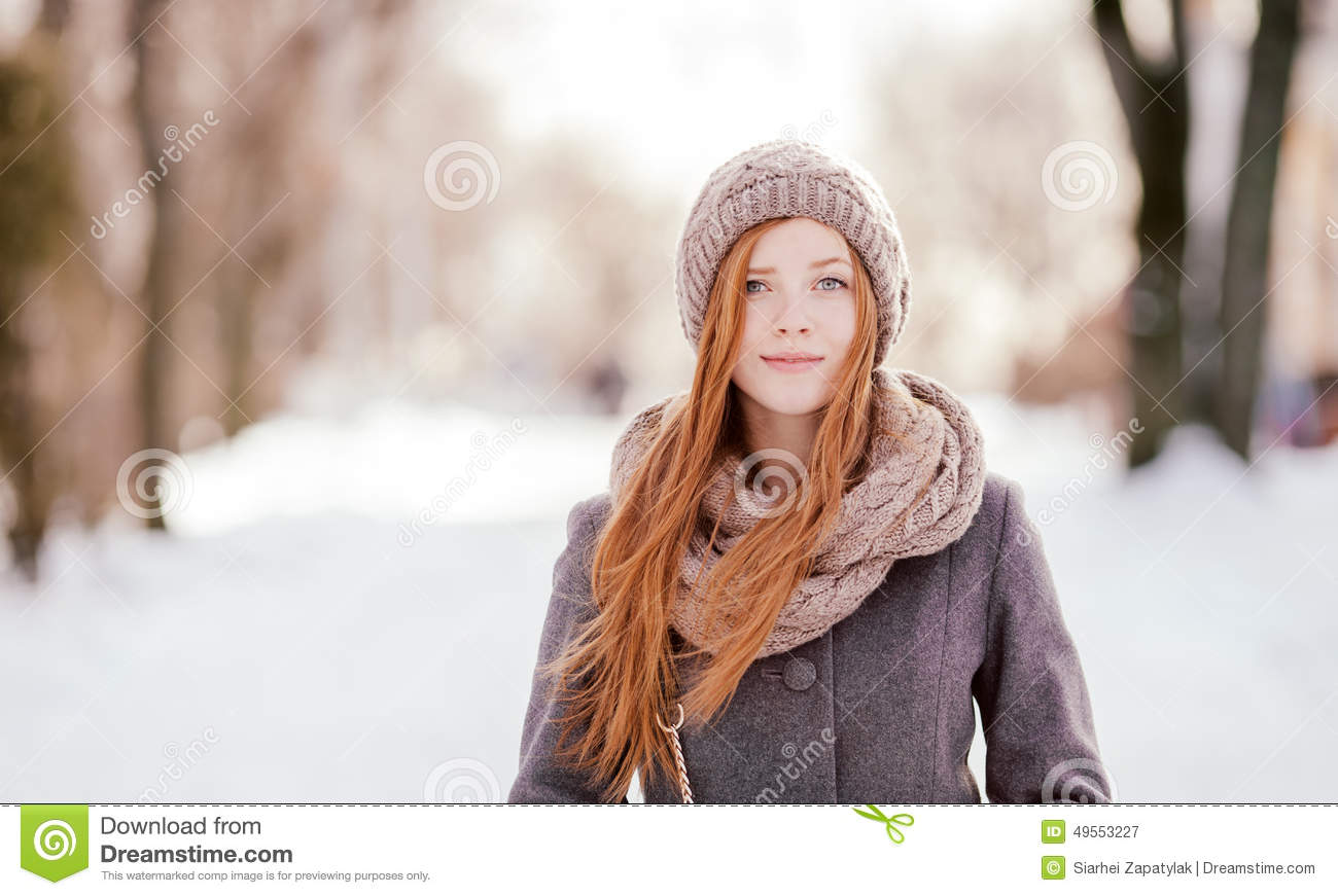 Winter closeup portrait of a cute redhead lady in grey coat and scarf posing in the park