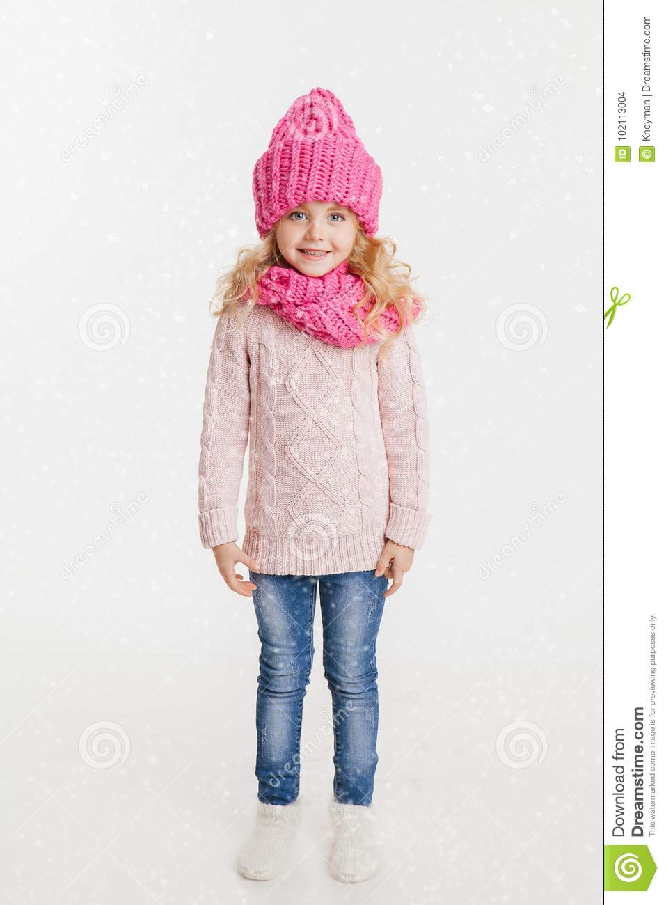 e82991470f5 Winter clothes. Portrait of little curly girl in knitted pink winter hat  and scarf