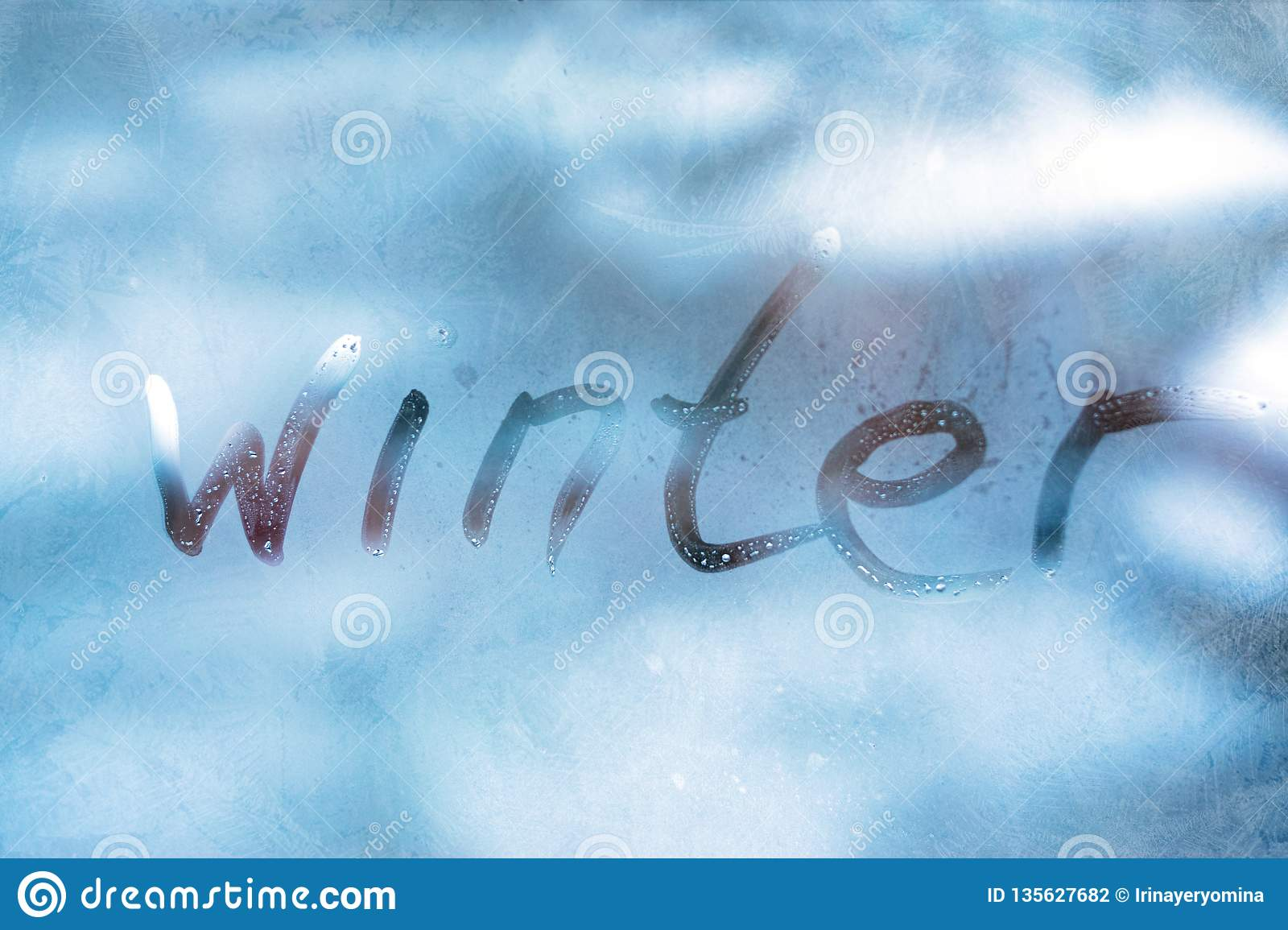 WINTER cold weather concept. Inscription word WINTER on the glass window with frozen patterns