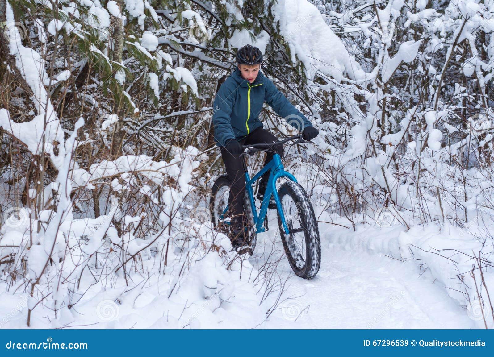 Winter, der in den Wald radfährt