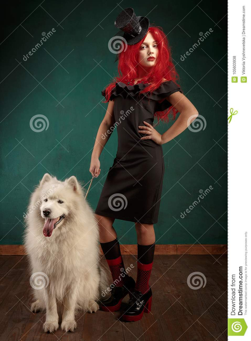 Winter dog holiday and Christmas. Girl in a black dress and with red hair with a pet in the studio. Christmas woman with