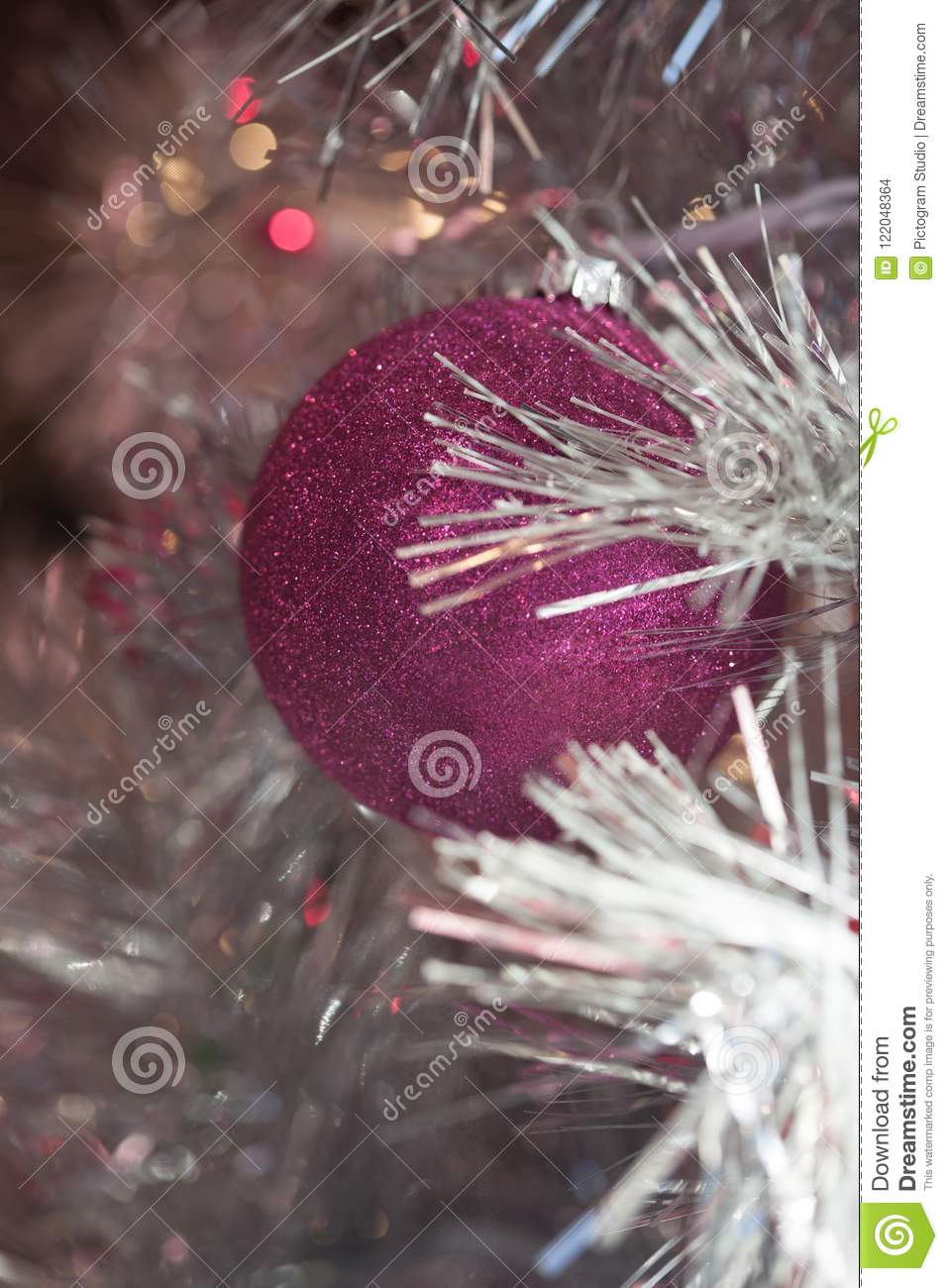 winter holiday silver white tinsel christmas tree with pink magenta ornaments and lights