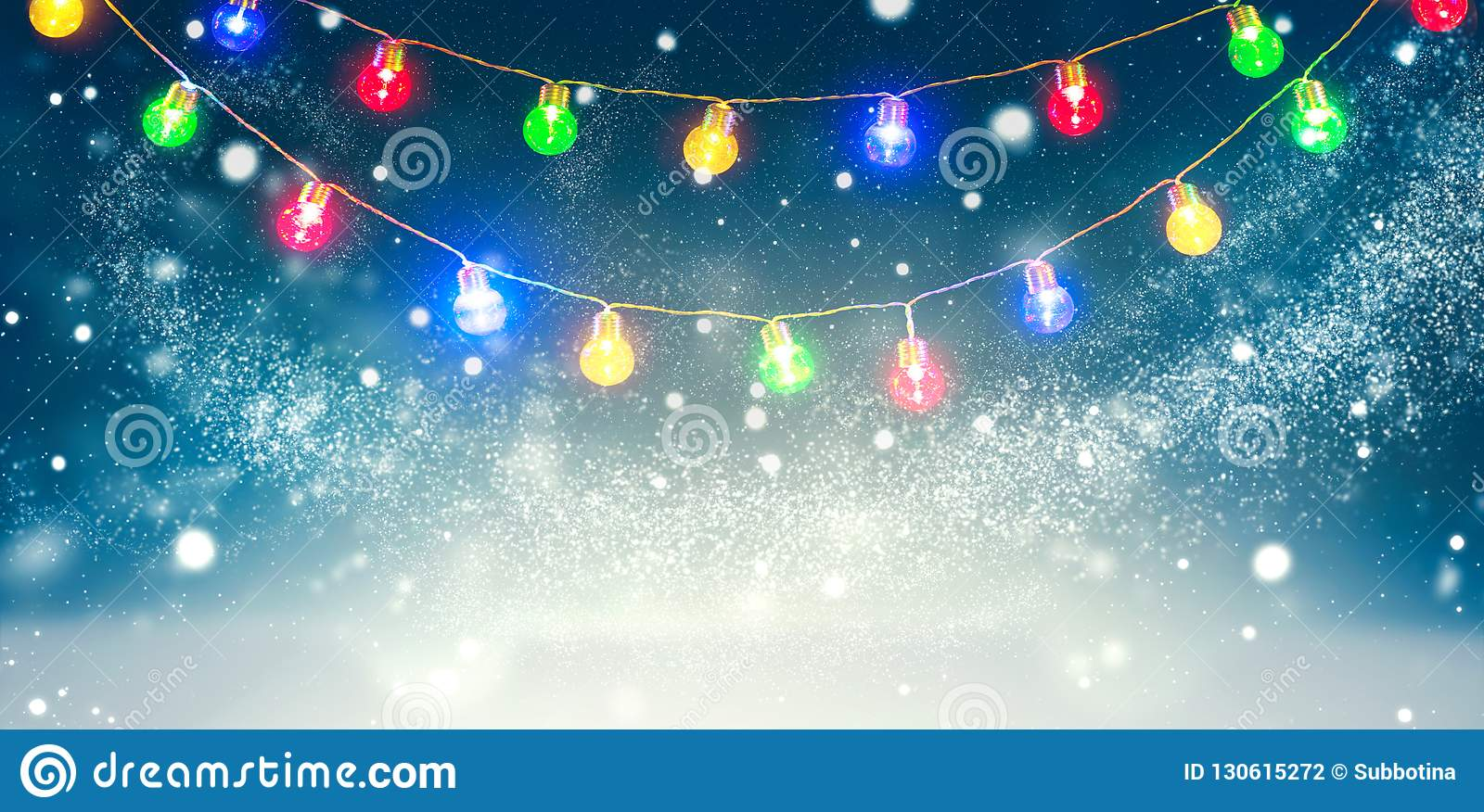 Winter holiday snow background decorated with colorful light bulbs garland. Snowflakes. Christmas and New Year abstract backdrop