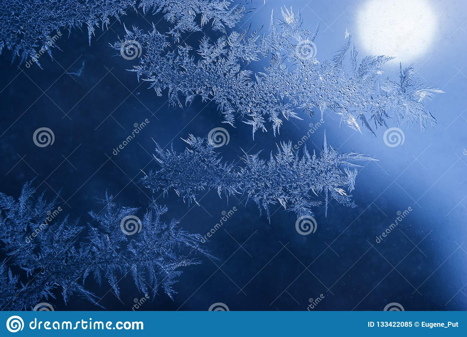 Winter Holidays Season Fantasy World Concept: Macro Image of Natural Ice Crystals Patterns on a Blue Frosted Window Pane With Sun