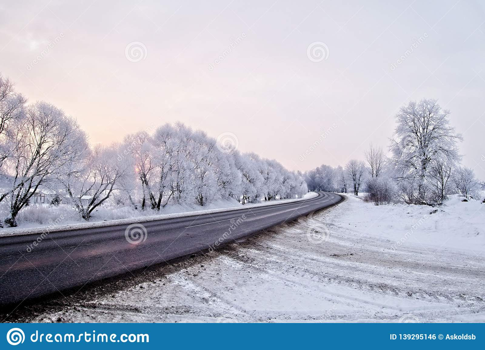 Winter landscape. Asphalted rural road at an early, cold winter sunrise - image
