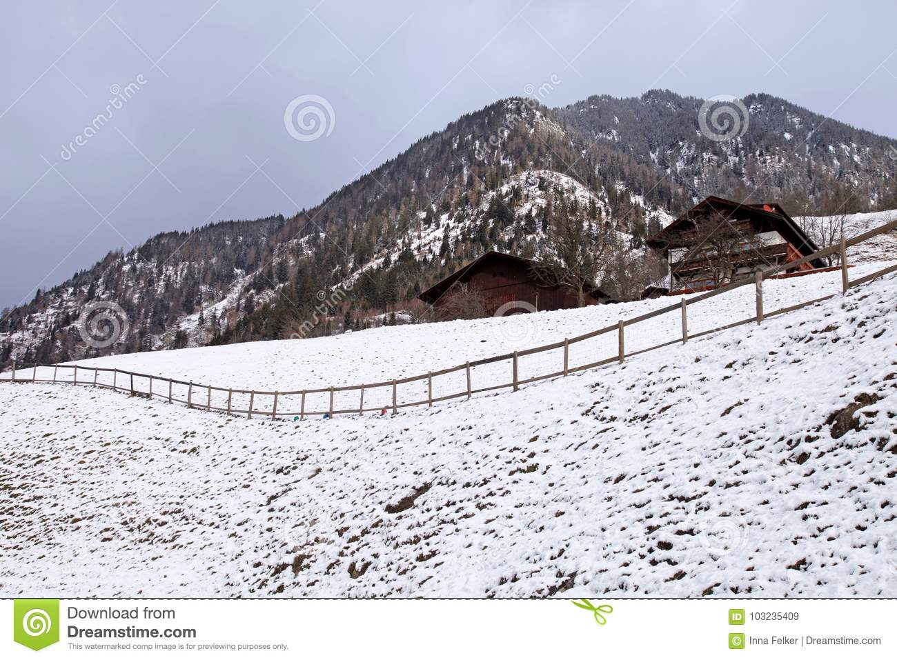 Winter landscape with wooden huts and mountain in small alpine v