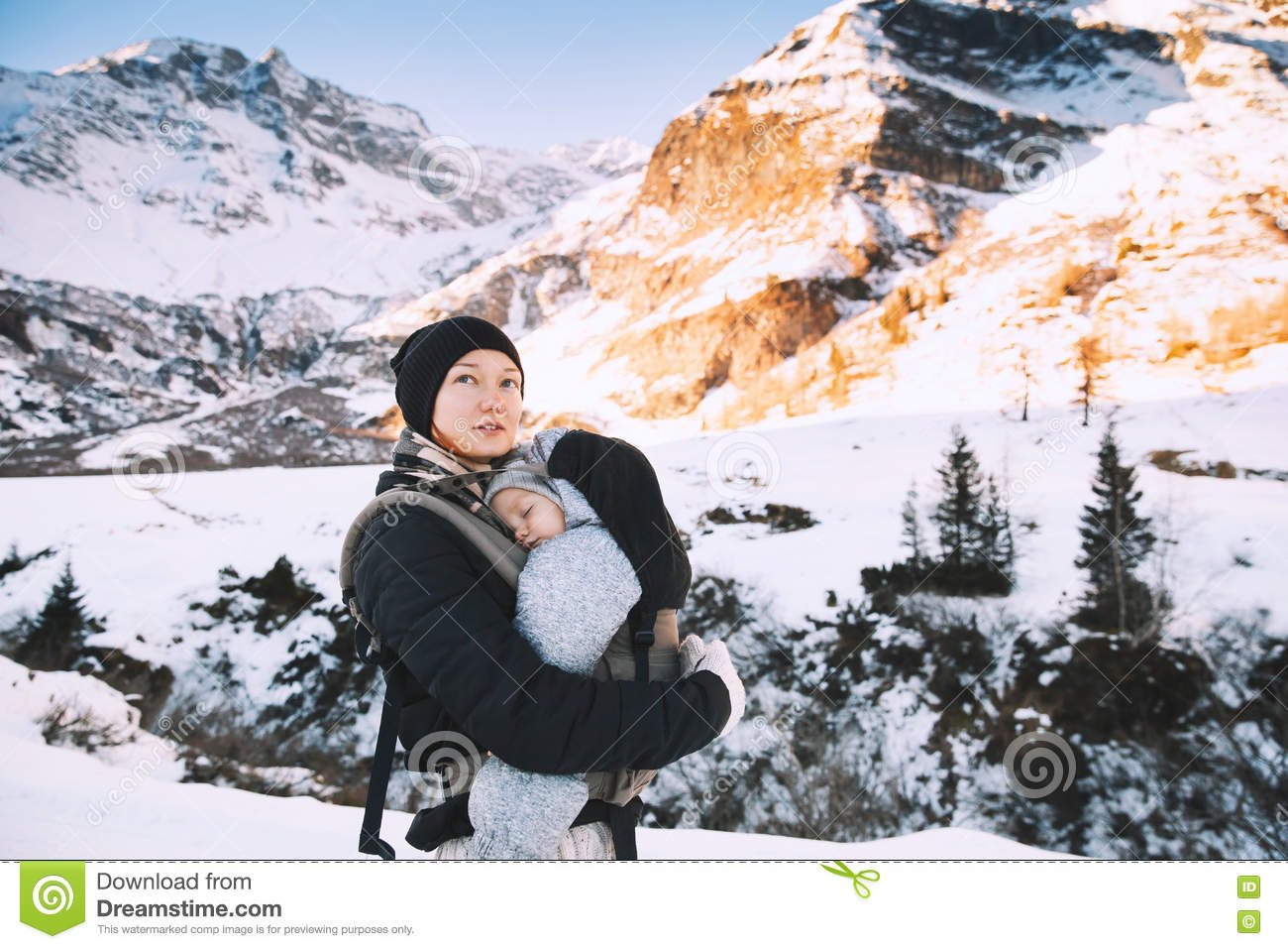 370329c0 Family of travelers walking in winter snowy countryside with mountain on  the background. Winter mountain hike in Austria. Active healthy mother with  her ...