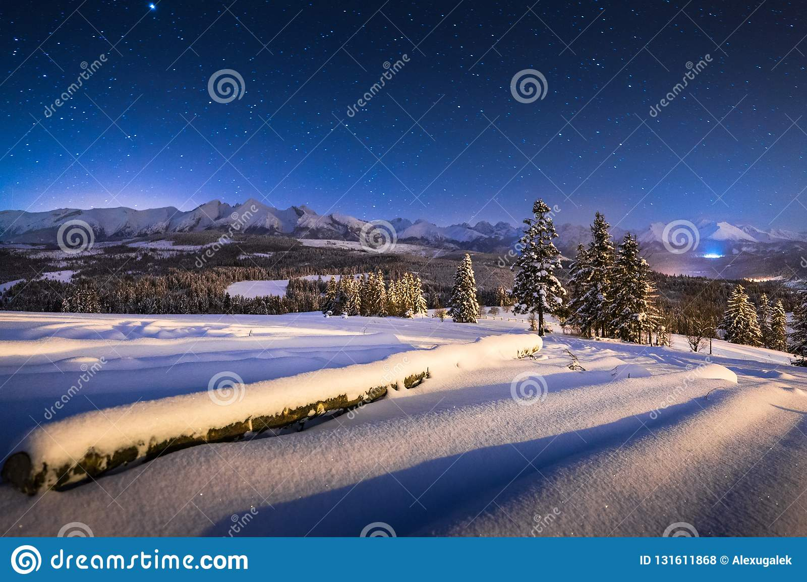 Winter night landscape. Starry blue night sky over winter mountains. Christmas night scenery in mountains