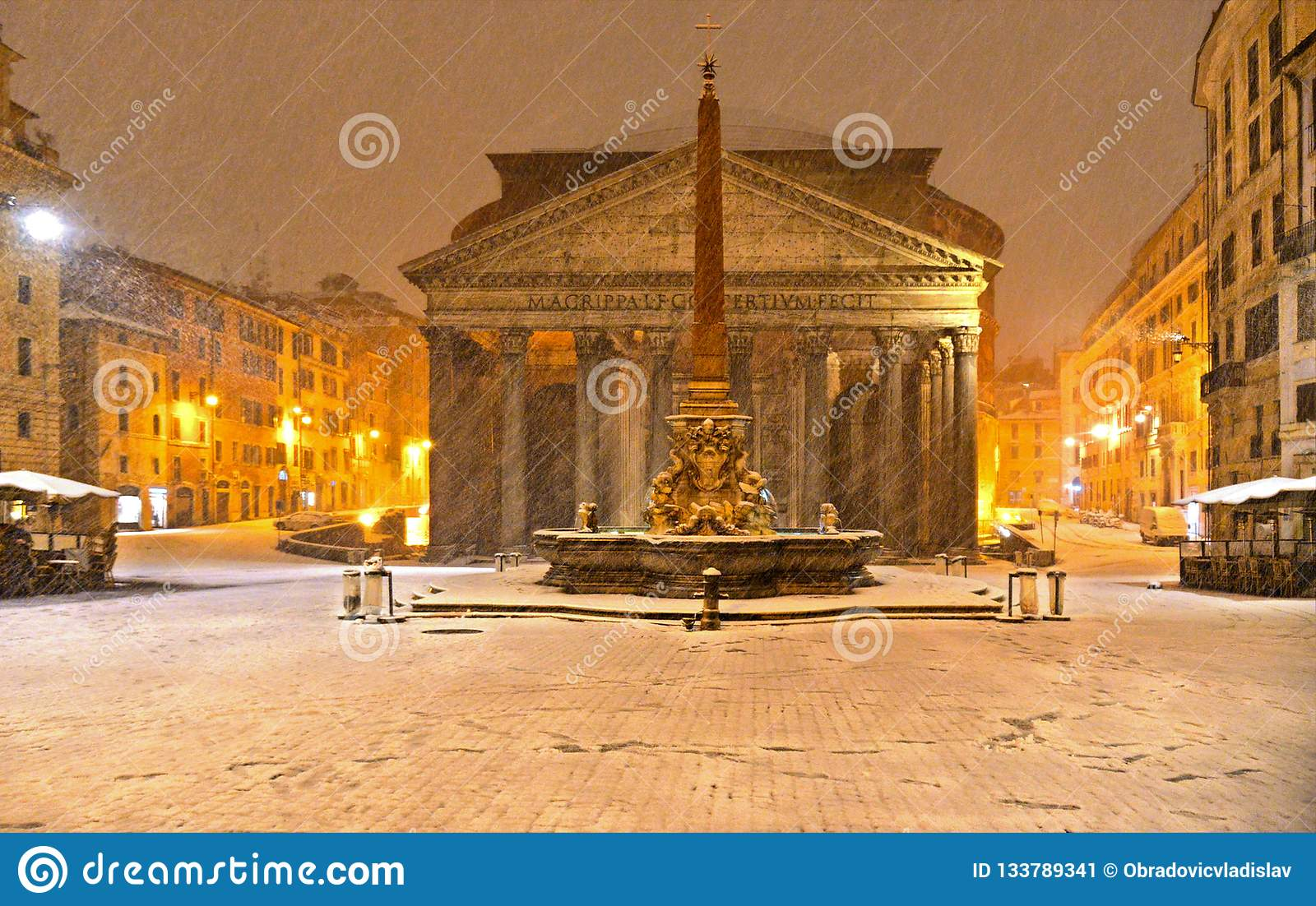 Winter night in Rome with snow blizzard and Pantheon temple church in empty square with golden light , Italy