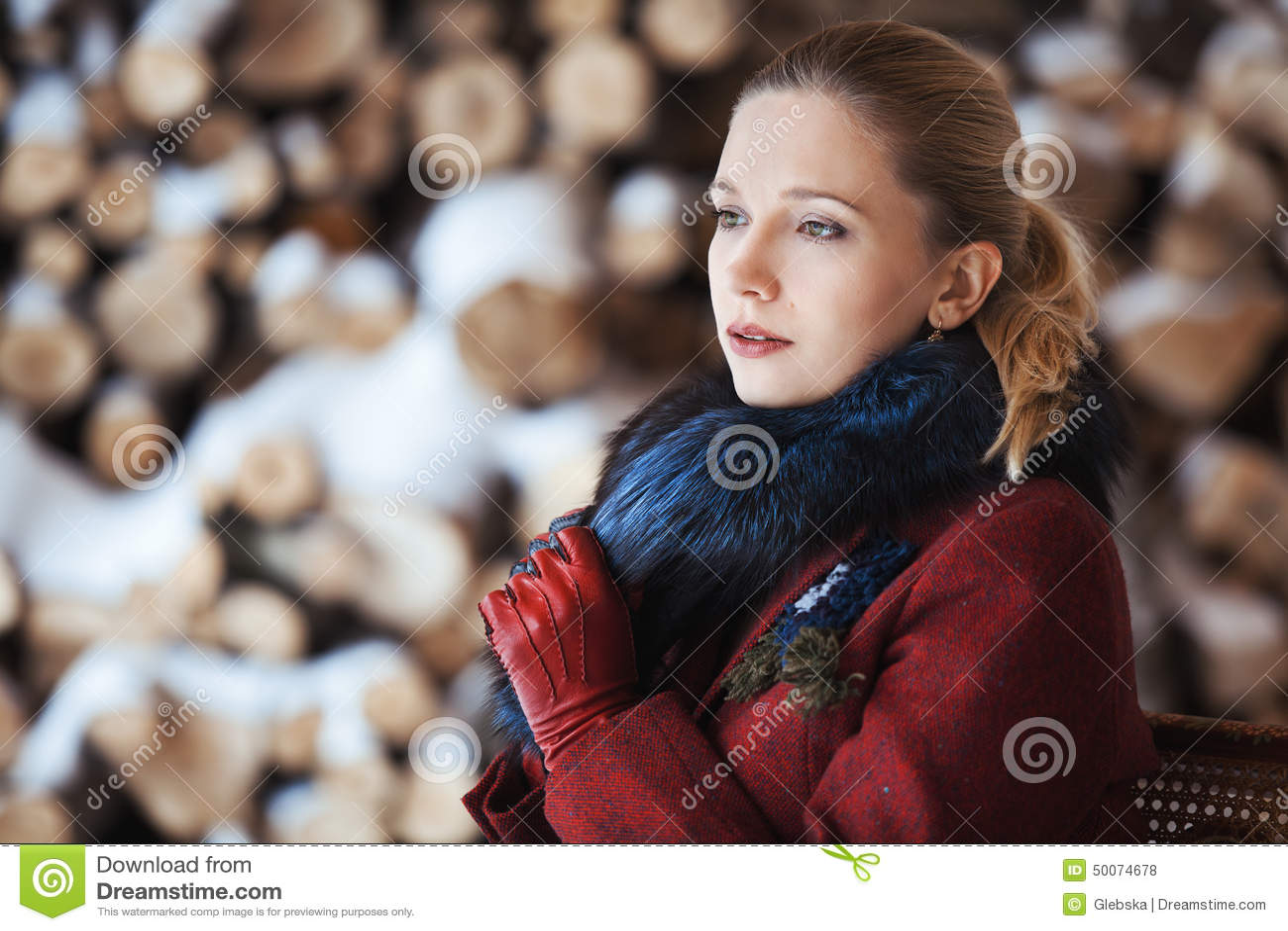 Winter portrait of blonde woman on firewood background