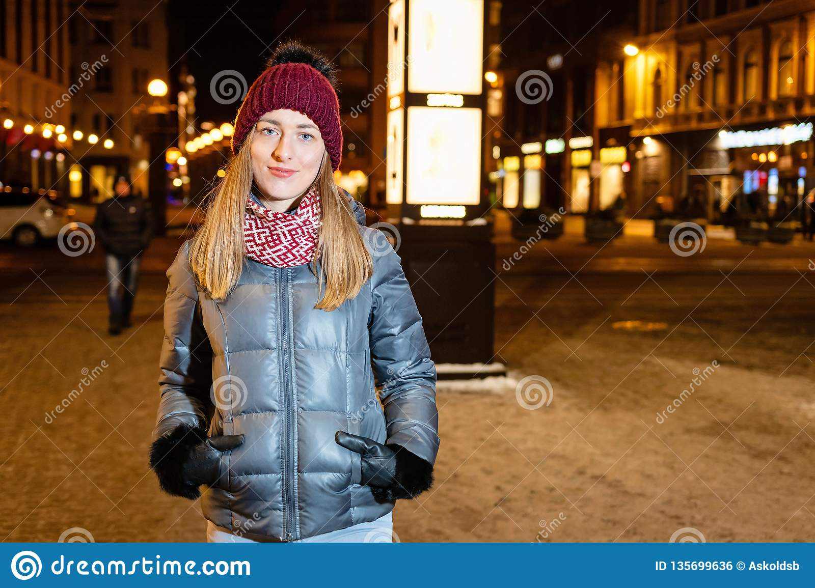 Winter portrait of happy young woman walking in snowy city decorated for Christmas and New Year holidays.