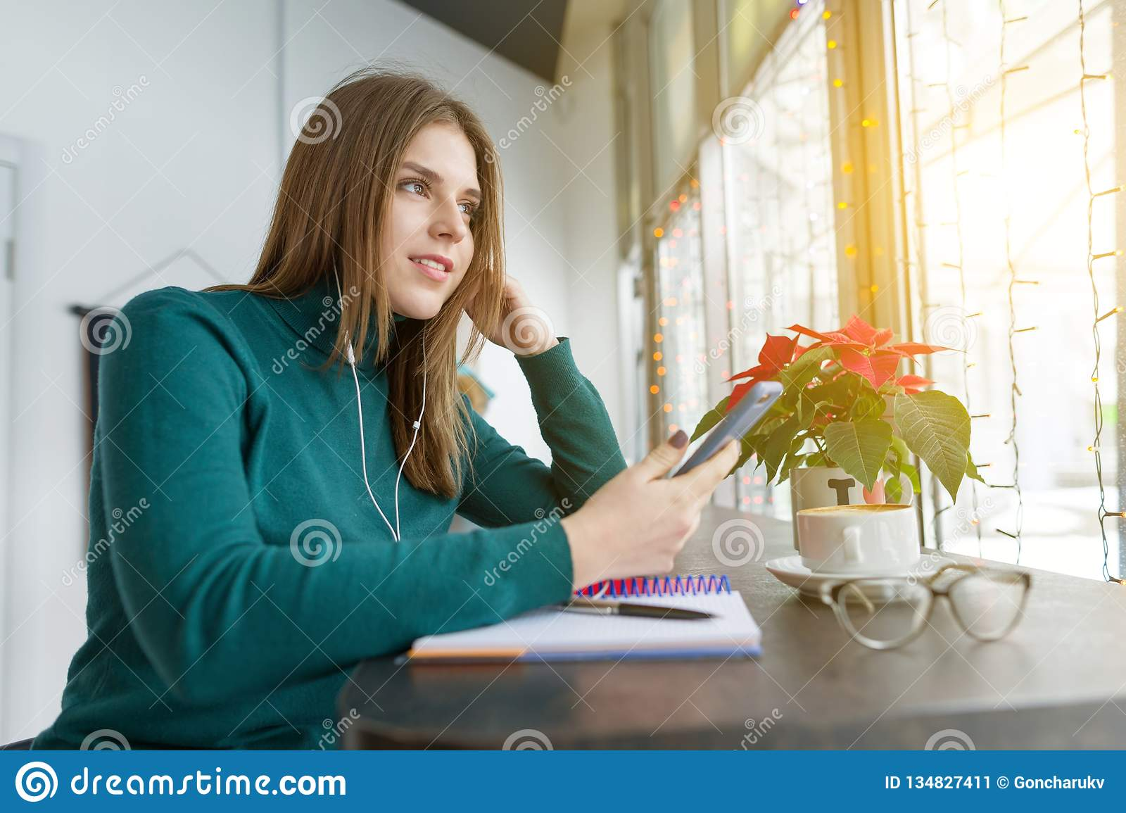 Winter portrait of student girl studying in cafe sitting with cup of coffee. Young woman studying using smartphone, listening to