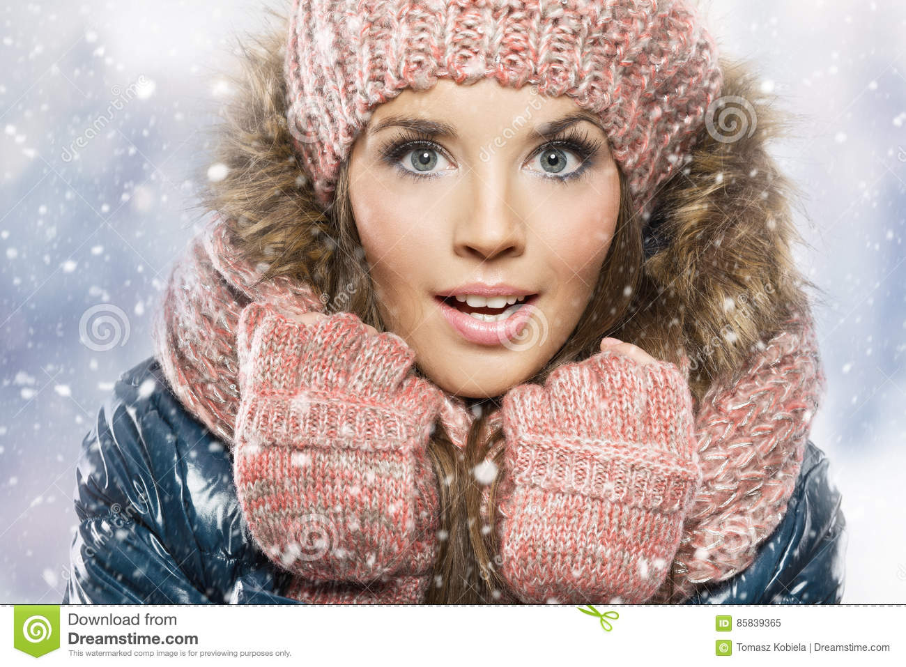 Winter portrait of young beautiful brunette woman wearing knitted snood covered in snow.